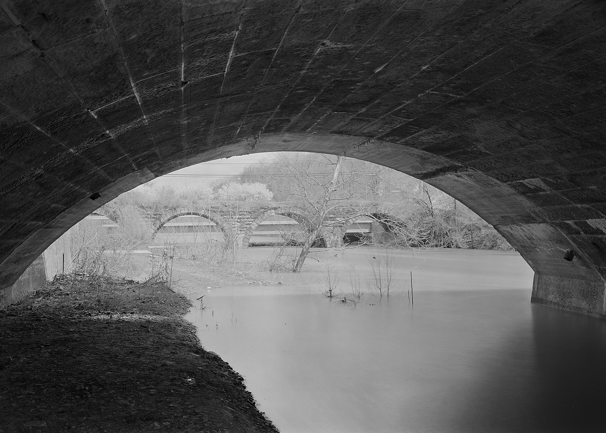 """Entering from the east the relocated mainline of the late 1890s runs along the former Public Works Canal alignment. Here at the mouth of Standing Stone Creek we are standing below the """"new"""" bridge looking north toward the remains of the original alignment and stone arch bridge that runs parallel to Penn Street."""