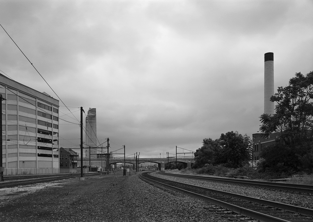View looking west in the vicinity of Harris Interlocking. Note the State Street Bridge which necessitated the revision of the trackage and the PRR's building of Harris Interlocking. Aptly named Memorial Bridge, the structure with massive art deco towers honors those who have served our Country in war. Harris Tower is center left between the parking structure and State Street bridge. The current Norfolk Southern mainline is on the right with the Amtrak connection to the left. Note the vast expanse of emptiness here including the catenary poles leading up to the overgrown areas on the right side of the bridge, this was once all part of the Harris Interlocking plant moving traffic in and out of the Harrisburg passenger station