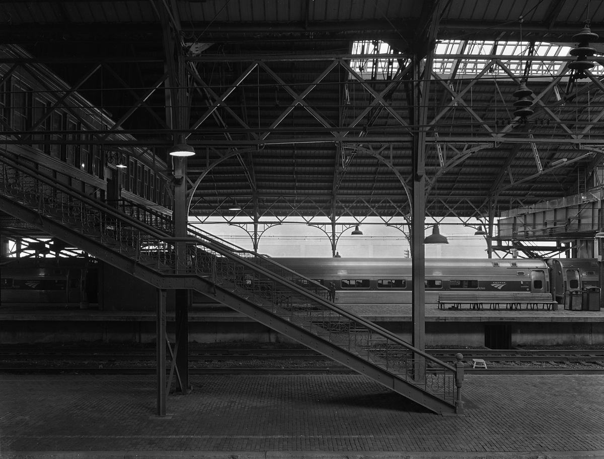 Train shed interior looking east. Notice the intricate iron work on the stair railings and trusses. The active center platform has been elevated to accommodate Amtrak/ ADA compliance needs but the remaining low level platforms are still traditional herringbone brick with stone curbs. This shed is one of few remaining examples of a style of station that was once commonplace in America.