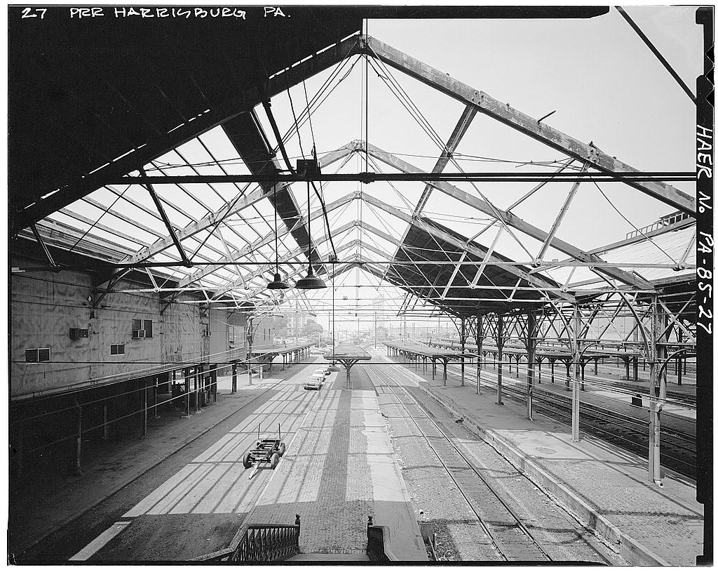 "View from photographer Harlen Hambright, taken during the 1981 HAER survey. Survey caption reads ""View, looking north (railroad west) under shed from concourse, showing exposed truss after shed roofing was removed."" Collection of the Historic American Engineering Record, National Park Service."