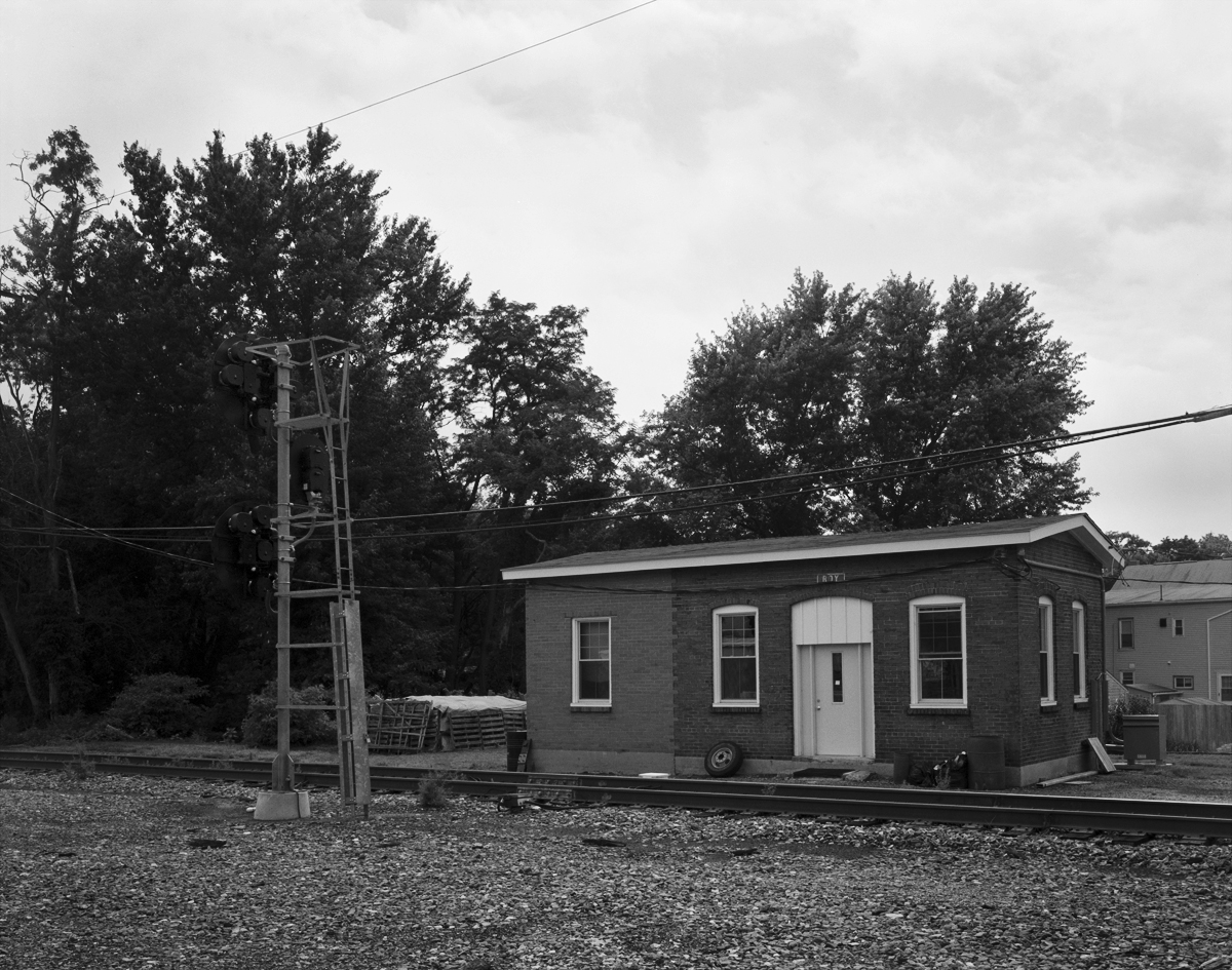 The single story brick building next to the westbound home signal protecting the Columbia Branch was a small yard office and maintainers building. The structure survives today to serve Amtrak C&S crews, having recently received new windows and an extension, evident by the different color brick on the left side of the structure.