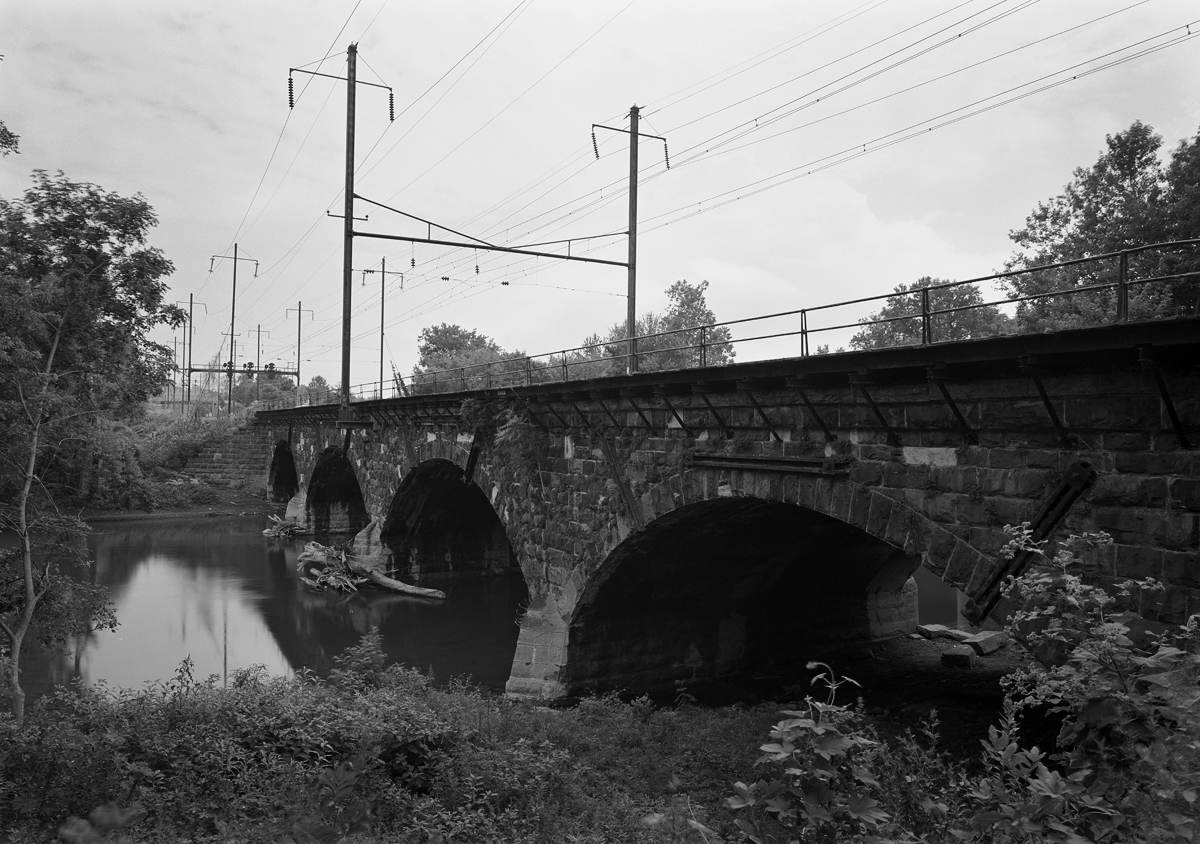A four arch stone bridge of Chief Engineer William H. Brown's design carries the mainline and Royalton branch over the Swatara Creek. In the distance is the home signals for Roy interlocking which marks the point where freight would diverge off the mainline south to Columbia.