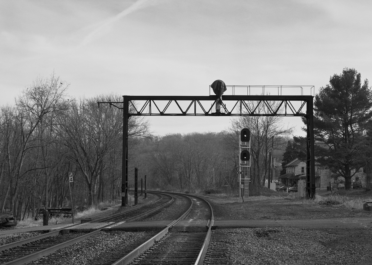 Former location of Cly block station and interlocking. The tower actually sat just around the curve, with this bridge supporting the eastbound home signals. Note the extra space on the right, this area was once four tracks wide with the Northern Central and York Haven Lines coming down from Enola.  Four miles east of here the NC would diverge from the York Haven Line at Wago Junction. This location was once part of the electrified low-grade line, evident by the cut steel posts on the left side of the tracks. Norfolk Southern has been doing considerable work here replacing rail, signals and general clean-up. After making this photo the former PRR signal bridge would fall, being cut up, further eliminating the visual clues that speak to the heritage of this line.