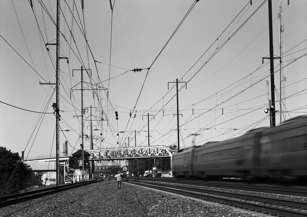 The PRR electrified network still serves the modern needs of Amtrak, providing propulsion for Acela, regional and local passenger rail service through out the Northeast. At Shore, on the Northeast Corridor a southbound passes as another northbound region approaches. Note the catenary above the void in front of the camera, this is where the line to Delair diverges and used to have multiple tracks, all electrified into Pavonia Yard in Camden.