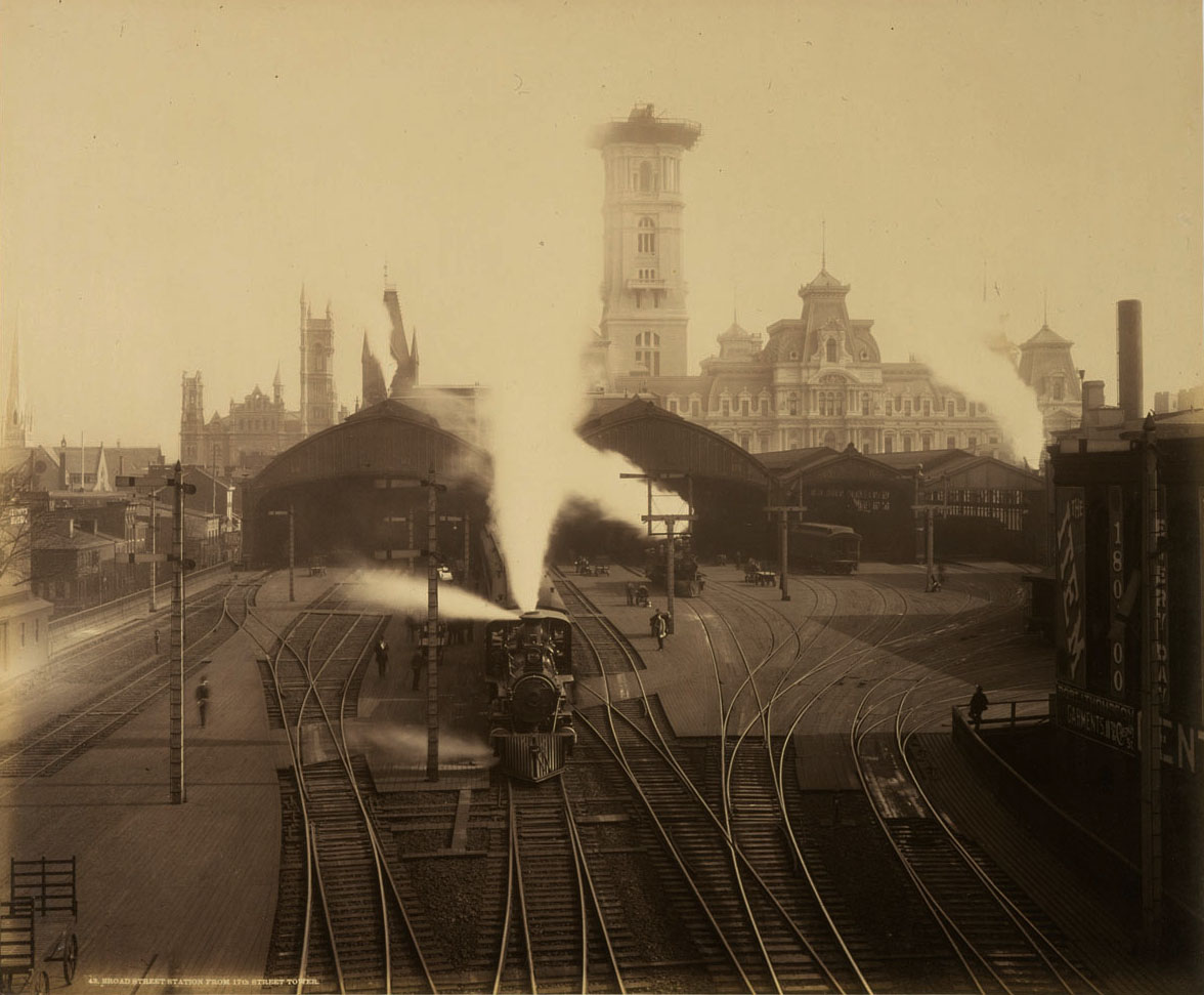 "1891 photograph of the original Broad Street Station reveals a terminal that is less than one year from undergoing ""modernization"" by noted architect Frank Furness. During that project the station would see the elimination of the multiple train sheds in favor of a single glass and iron shelter covering 16 tracks that measured roughly 600' long, 300 wide and 100 feet above the tracks. Note the ongoing construction of  Philadelphia City Hall, including the pedestal that the iconic William Penn statue will stand on. William H. Rau photograph, Collection of American Premier Underwriters, Inc."