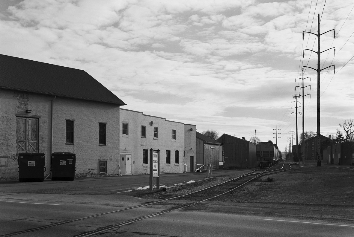 This surviving segment of the Reading and Columbia branch crosses Main Street in Salunga-Landisville south of the connection with the PRR continuing to the East Hempfield Township line to serve several industries. Today this industrial track is served by Norfolk Southern crews and includes several consignees like the lumber yard immediately behind the photographer.