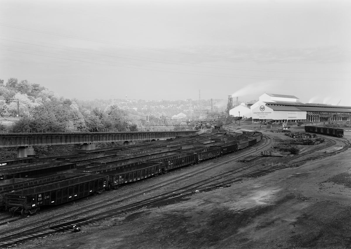 East end view of the Edgar Thompson Works reveals one of the remaining blast furnaces which produce the raw steel to feed the Mon Valley Works which includes finish mills in Irvin and Fairless Hills, Pennsylvania. The complex rail infrastucture required to feed the mils is illustrated here: In the foreground there are staging yards for gondolas of scrap steel, the ram bridge that connects the ET Works to the Union Railroad main line, the Union RR right of way left center (note signal gantry) all of which are on the bank of the Turtle Creek.
