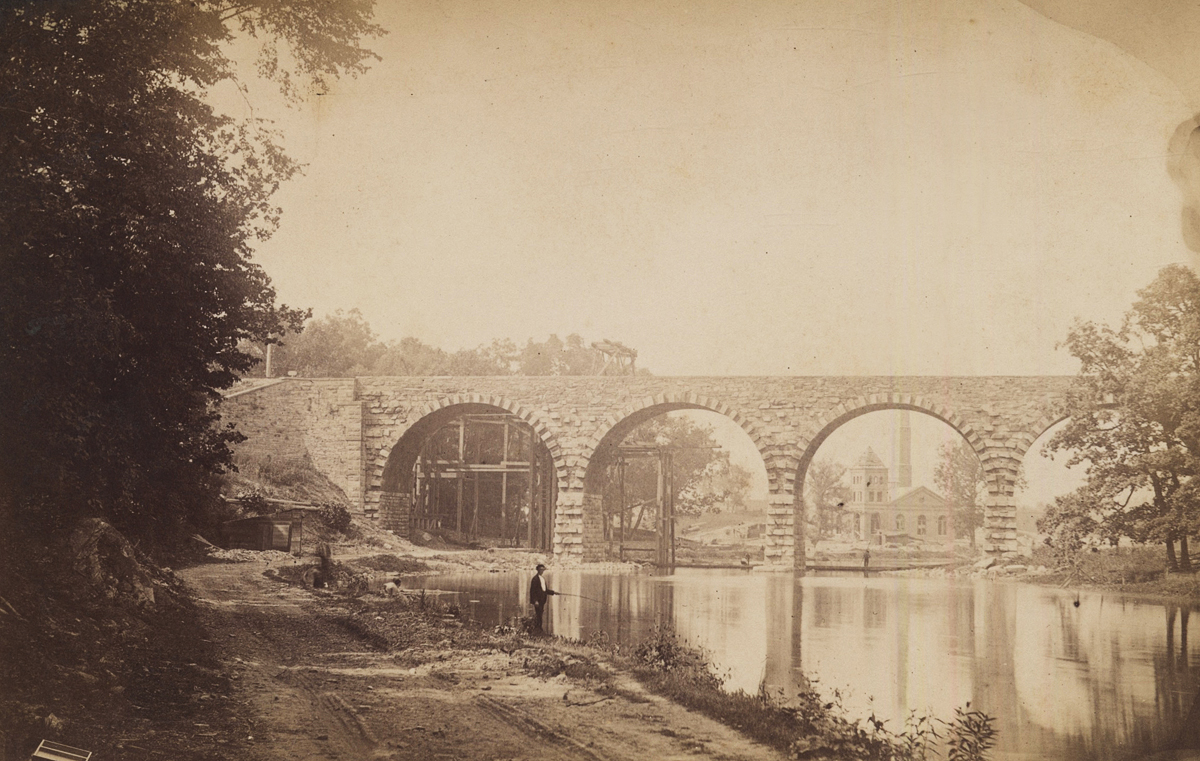 One of many early improvements in the Lancaster terminal area was the stone bridge over the Conestoga River where the main line from the east entered Lancaster. Designed by Chief Engineer William H. Brown and completed in 1887 the two track Conestoga Bridge is unique in its design as the south side was left with protruding stonework to allow for further expansion had the railroad required additional capacity. Though this bridge was an operational bottleneck when the mai nline east was four-tracked subsequent construction of the Atglen and Susquehanna branch alleviated much of the through freight congestion in the Lancaster area. Image courtesy of LancasterHistory.org, Lancaster, Pennsylvania.