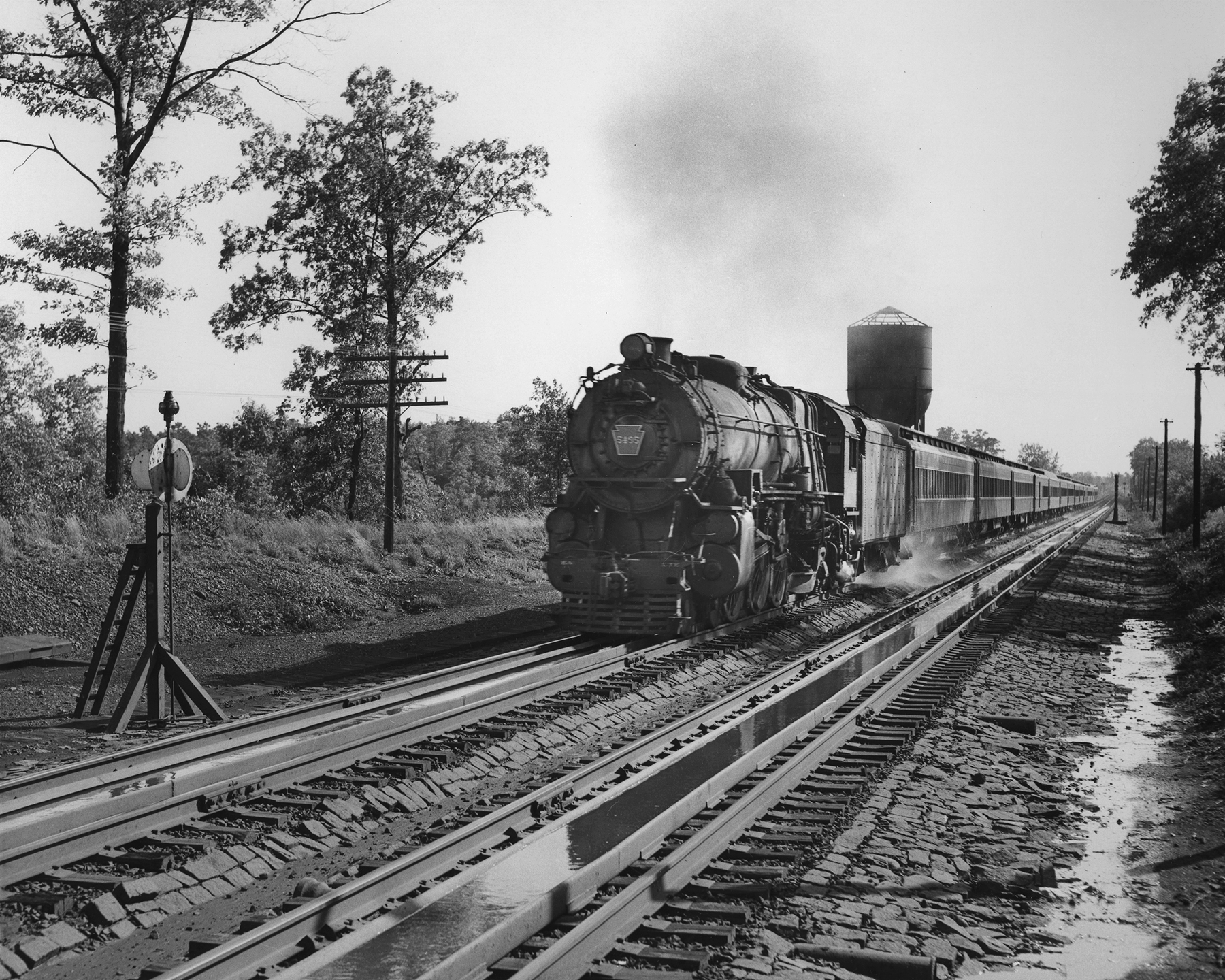 Pennsylvania Railroad Class K4 Pacific 4595 takes on water from track tanks inside the gage of the rail at Ancora, New Jersey. The track tanks allowed steam engines to take on water at speed to avoid lengthly service stops and tying up the main line and were once a common practice in many places along parent road, Pennsylvania Railroad. The ubiquitous PRR Class K4 was one of many locomotives the parent company provided to the PRSL for service.Photography by Robert L. Long, Collection of William Gindhart