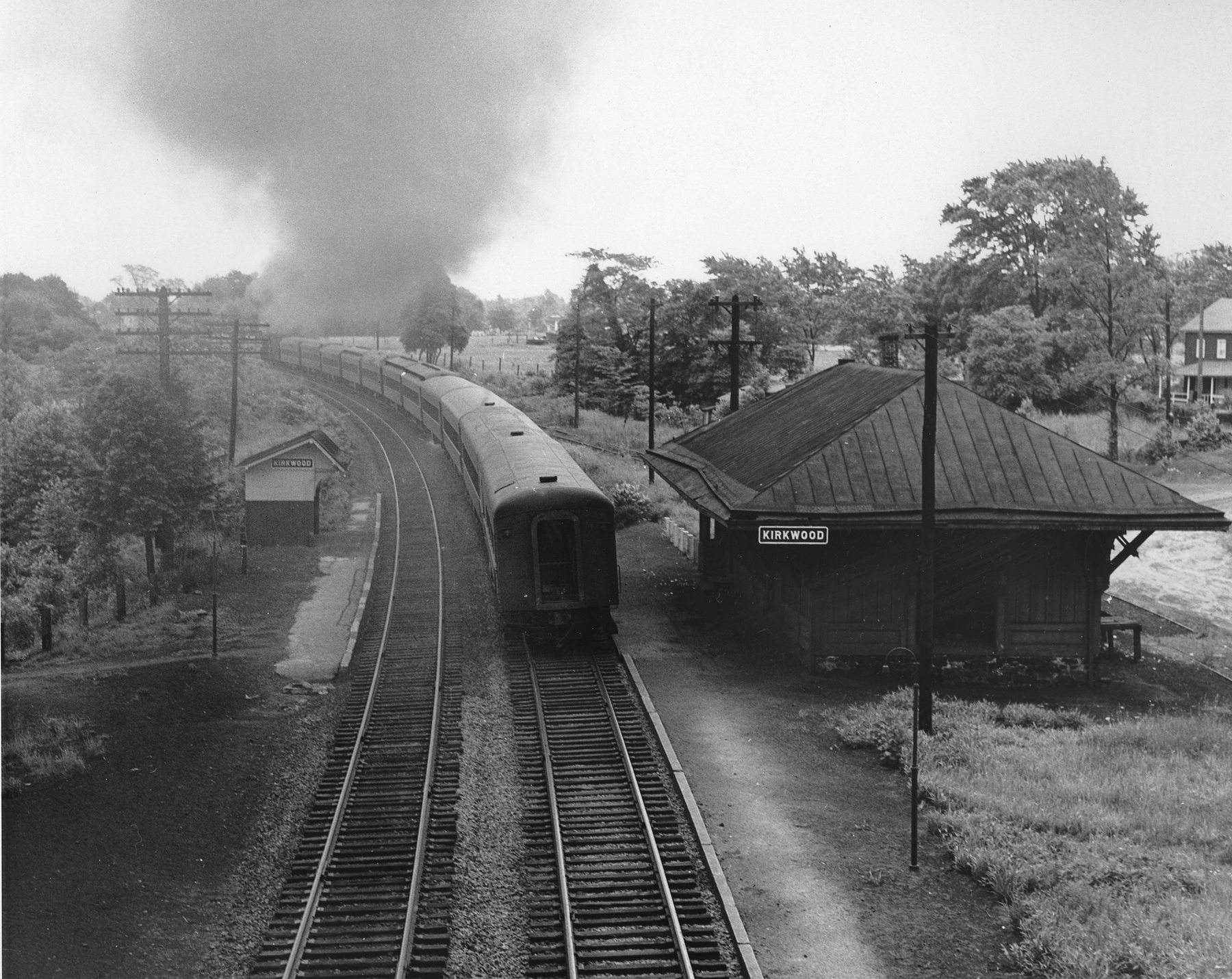 Southbound PRSL train passes through Kirkwood, New Jersey with PRR K-4 class locomotive 8746 and eleven cars, circa Summer of 1950. The Kirkwood station is actually where the modern day Lindenwold Station is for both New Jersey Transit and the PATCO high speed line.Photography by Robert L. Long, Collection of William Gindhart