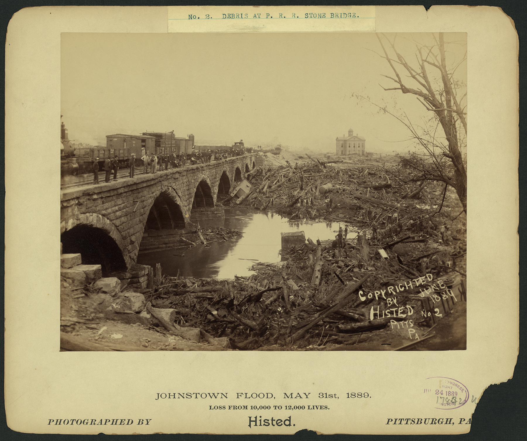 "The great stone bridge on the Pennsylvania Railroad's main line played a large role in the devastation during the flood when debris washed across the valley piling up against the bridge creating an unintended dam, trapping flood victims in a 70' high debris pile that burned for three days. After the fire and flood water subsided clearing of the bridge required the expertise of ""Dynamite Bill"" Flynn and a 900 man crewtaking 3 months to complete the task. Photograph by Ernest Walter Histed, collection of the Library of Congress."