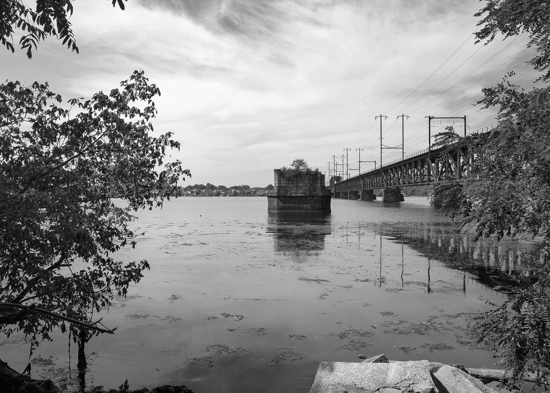 Susquehanna River Bridge, Perryville, Maryland. Images like this provide the visual clues of the evolution of the PRR network; the surviving piers of the 1866 Philadelphia, Wilmington & Baltimore Railroad bridge spanning the Susquehanna stands adjacent to its replacement completed by the Pennsylvania Railroad in 1906. Learn how I draw inspiration from historical imagery to create contemporary images that explore the surviving infrastructure of the PRR while considering its impact on the surrounding landscape.