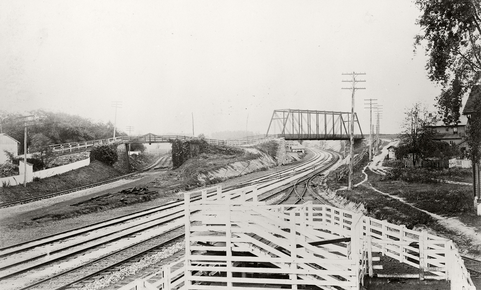 View looking west from the mainline, showing the old (left) and new (right) alignments of the right of way. Soon the old right of way and overpass would be removed. Cattle pens and a siding in the immediate foreground are in the vicinity of the freight house which still stands today. Note the absence of the fourth track which indicates that this view was before 1895. Library of Congress HAER collection.