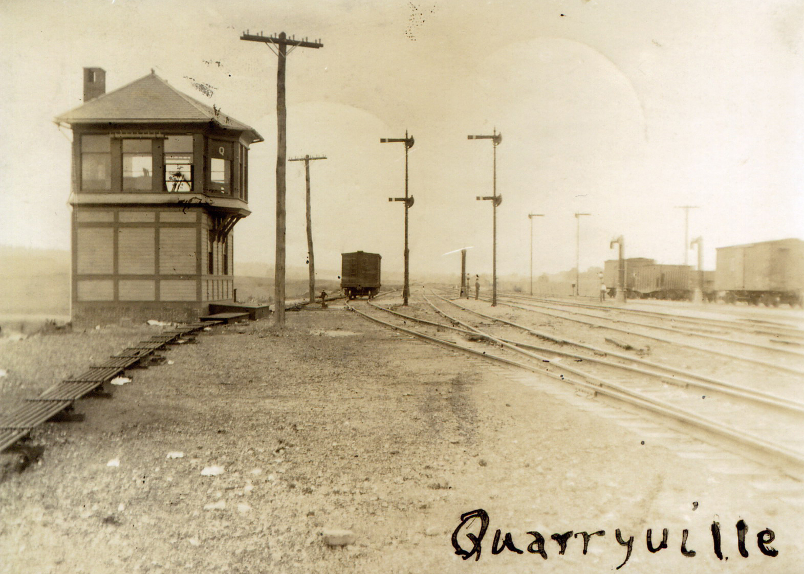 "This 1906 view shows the wood frame tower at Quarryville (Milepost 10.8), the first interlocking tower west of Parkesburg. ""Q"" had control over the two main tracks and four additional sidings to manage helper movements assisting trains to Mars Hill Summit. Additionally, four water columns were available to top off steam locomotive tenders on their journey east or west. Image collection of William L. Seigford"