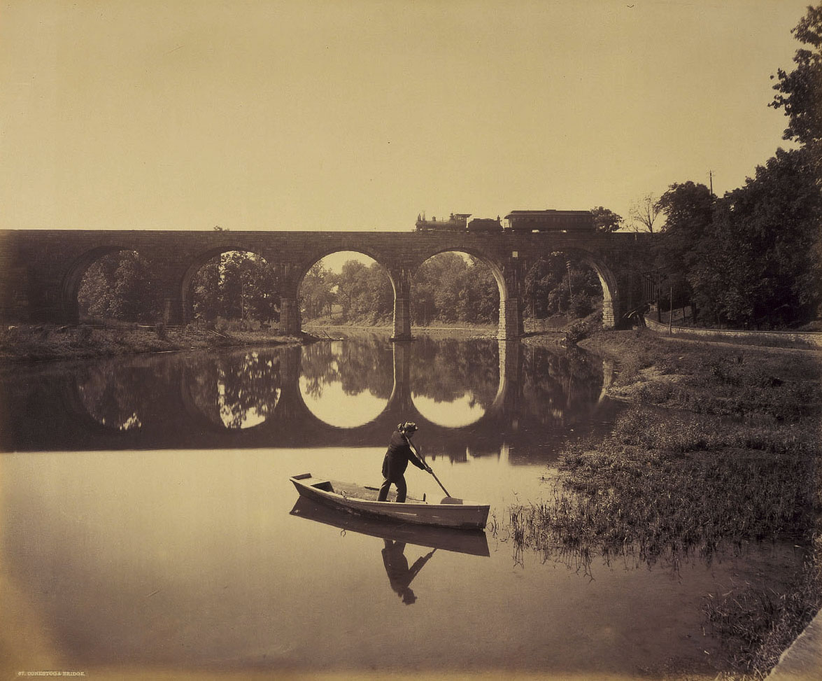 In a beautiful image by William H. Rau, we see the Conestoga River bridge, one of Brown's first stone bridges. Utilizing the figure and boat as a device for scale in the foreground Rau is looking south, as noted by the finished facade of the bridge. To the left out of view is the Lancaster Water Works which still survives today. Photograph collection American Premier Underwriters, Inc.