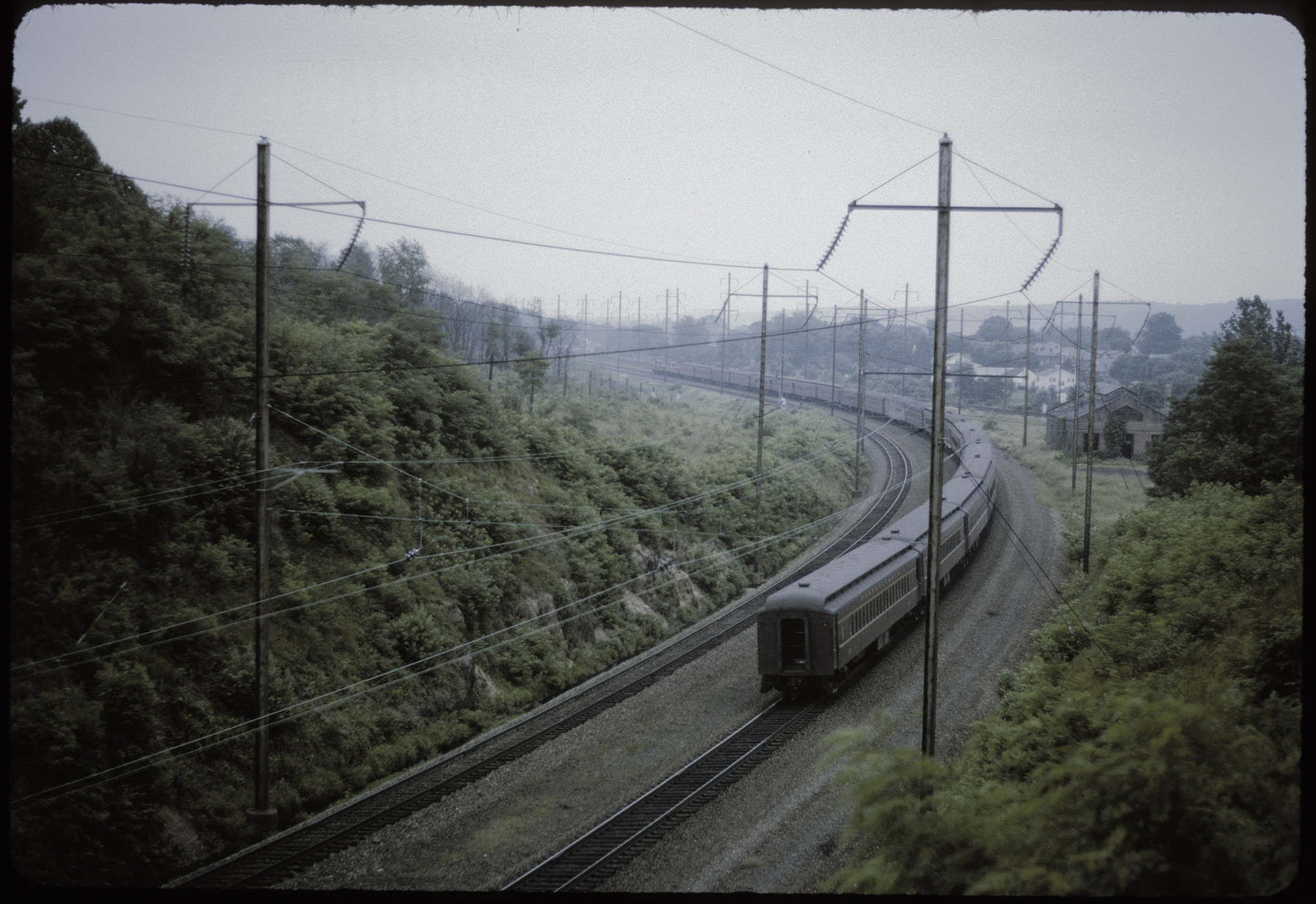 This 1962 view of an eastbound passenger train winding through the curve at North Bend shows evidence of the PRR's rationing of excess capacity with the removal of two of the four main tracks. While the era of steam has long since passed, a coal-fired boiler house remains, off to the right, once part of the extensive Atgen track pan system that allowed steam trains to take water at speed on both the Main Line and Atglen & Susquehanna Branch (visible behind the structure). James P. Shuman photograph, Railroad Museum of Pennsylvania, PMHC.