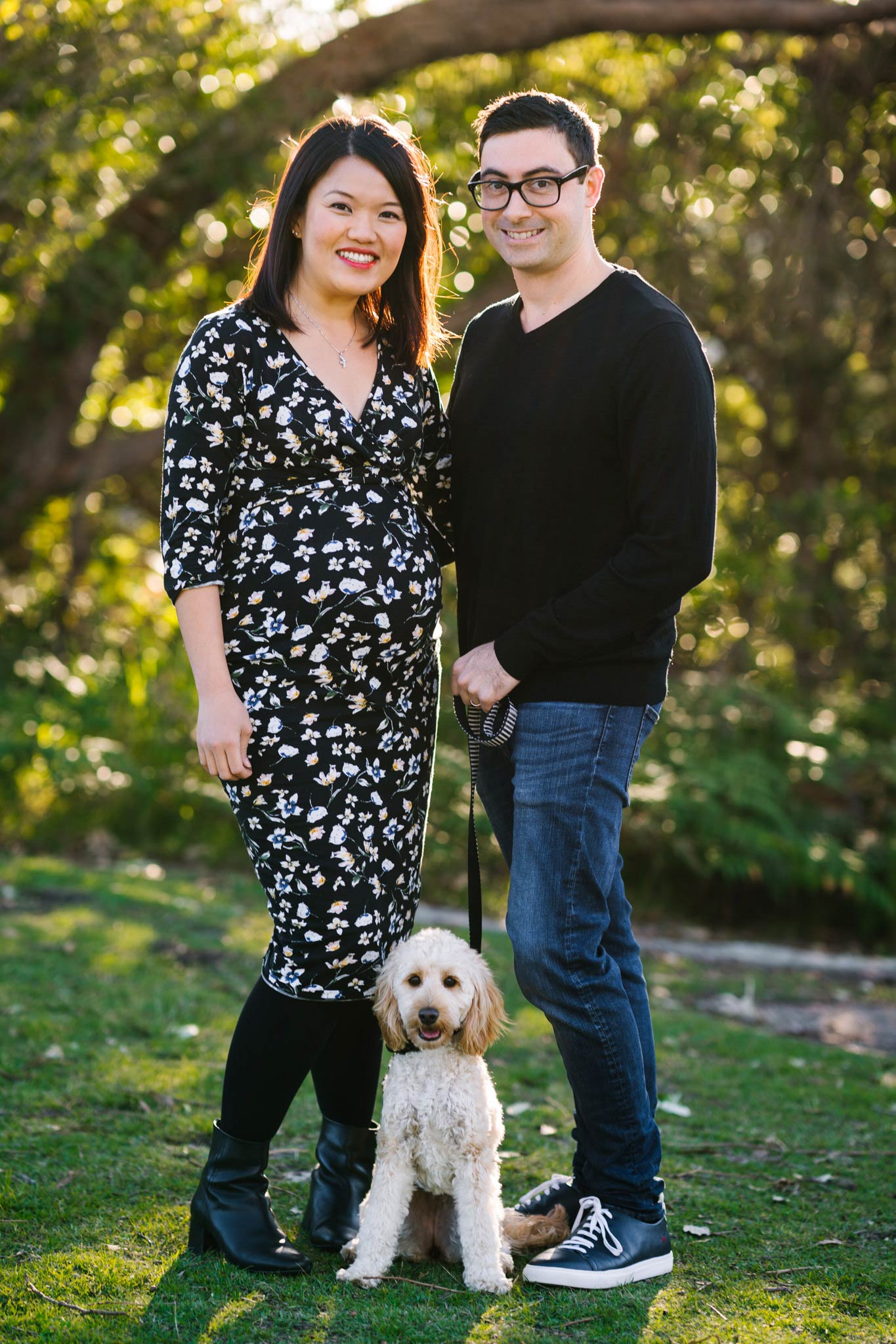 Pregnant couple posing with their poodle puppy