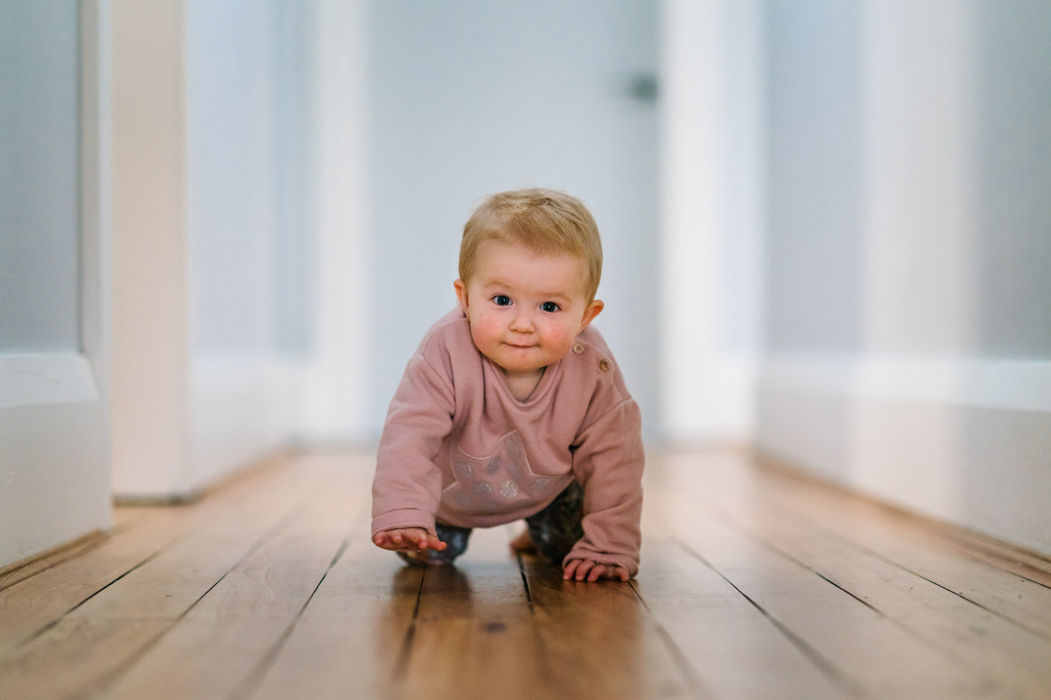 Baby crawling down hallway with cute look on her face