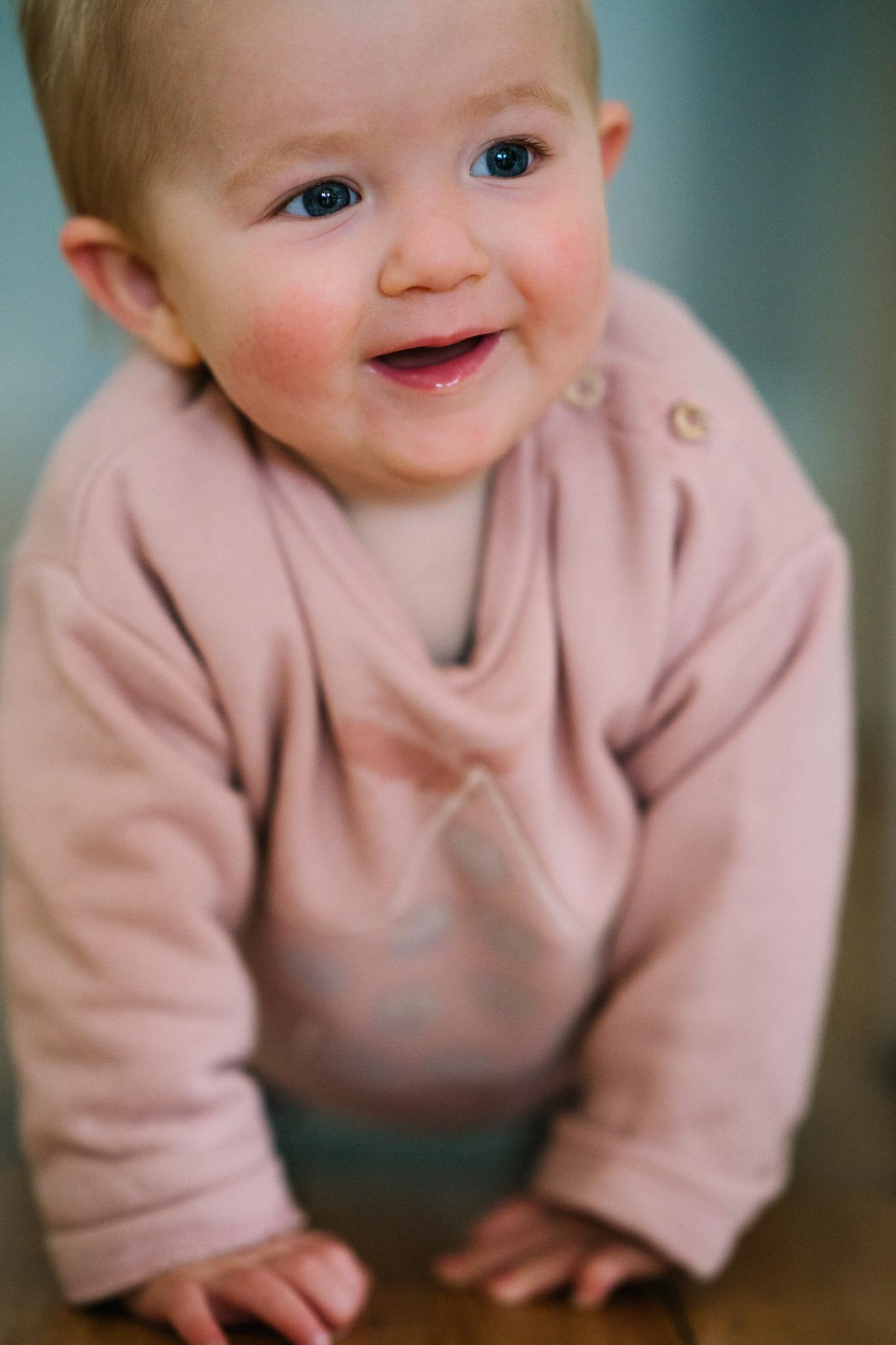 Baby smiling as she crawls towards camera