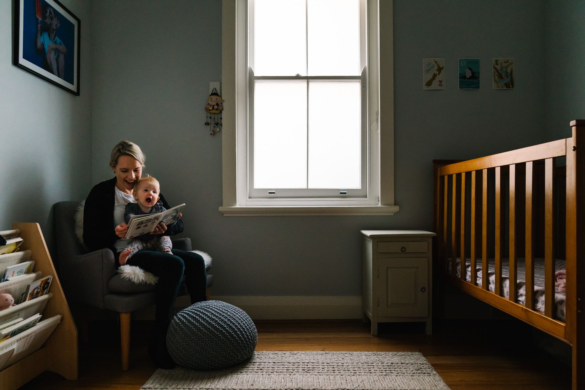 Mum and baby reading a book in a pretty nursery