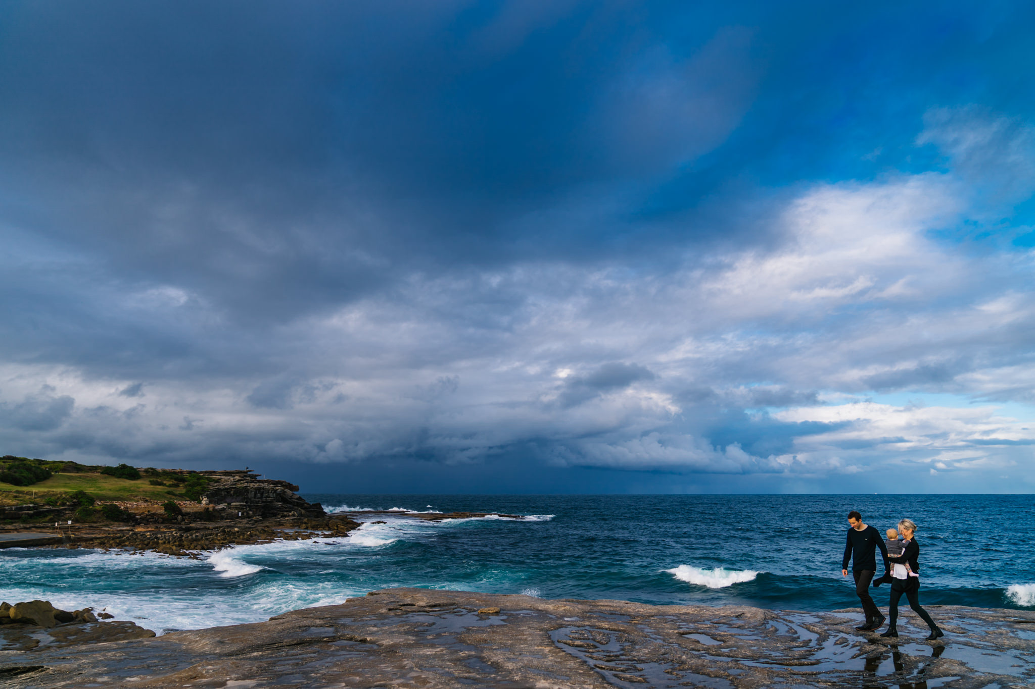 Stormy skies over Coogee beach as family walks along the rocks