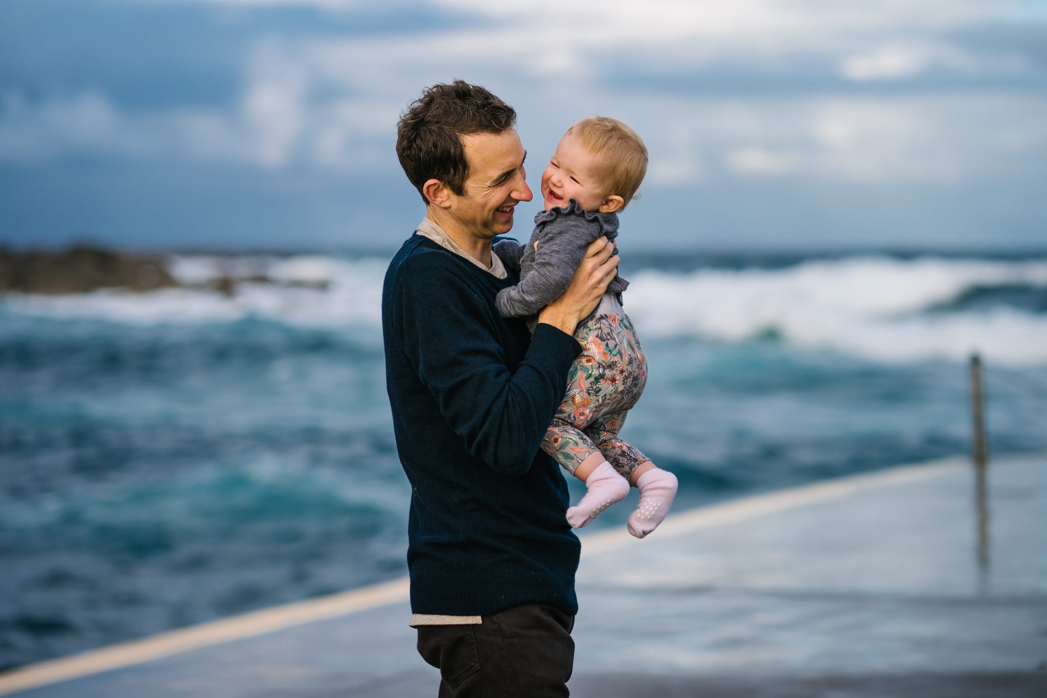 Baby and dad playing during Coogee Beach family photo session