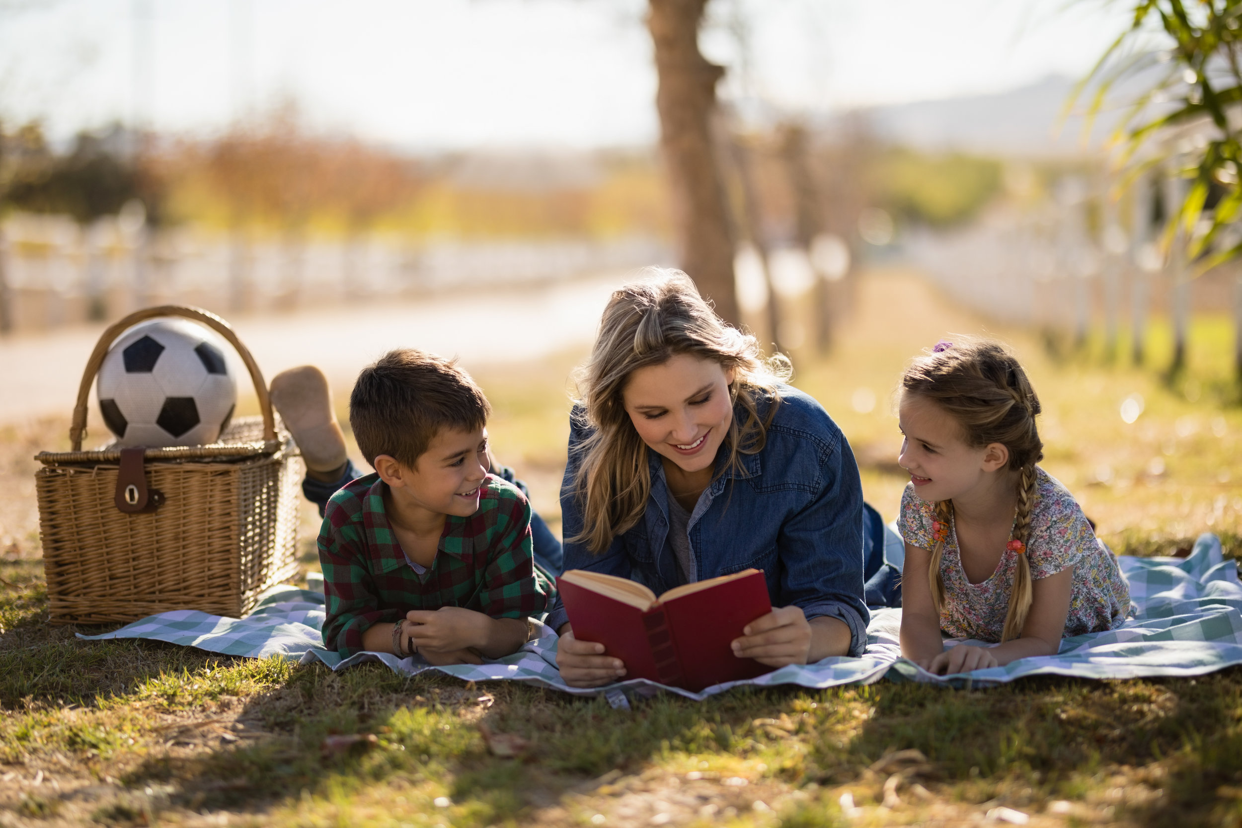 mother-and-kids-reading-novel-in-park-7CRSNZW.jpg