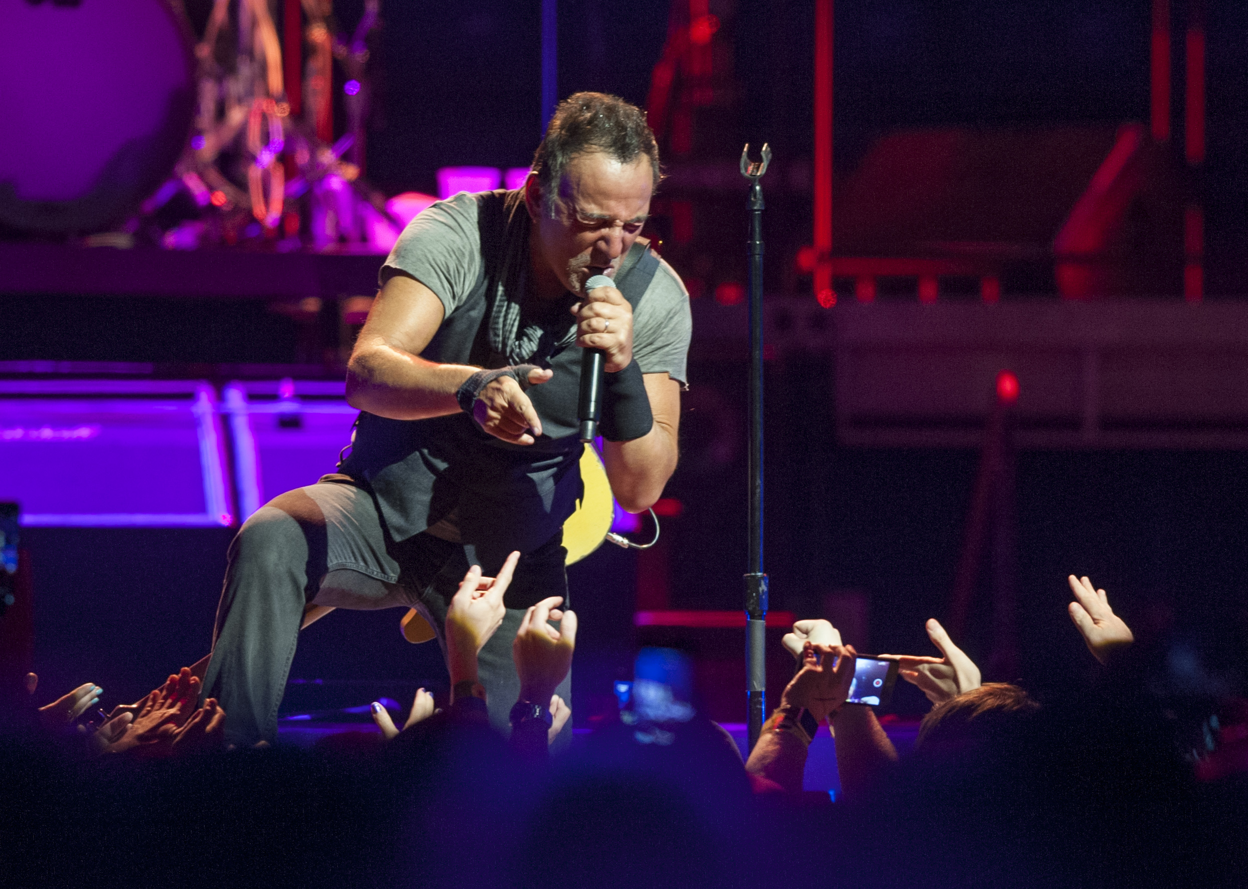 Bruce Springsteen climbs down to sing to his fans during his performance at the Bryce Jordan Center on Monday, April 18, 2016.