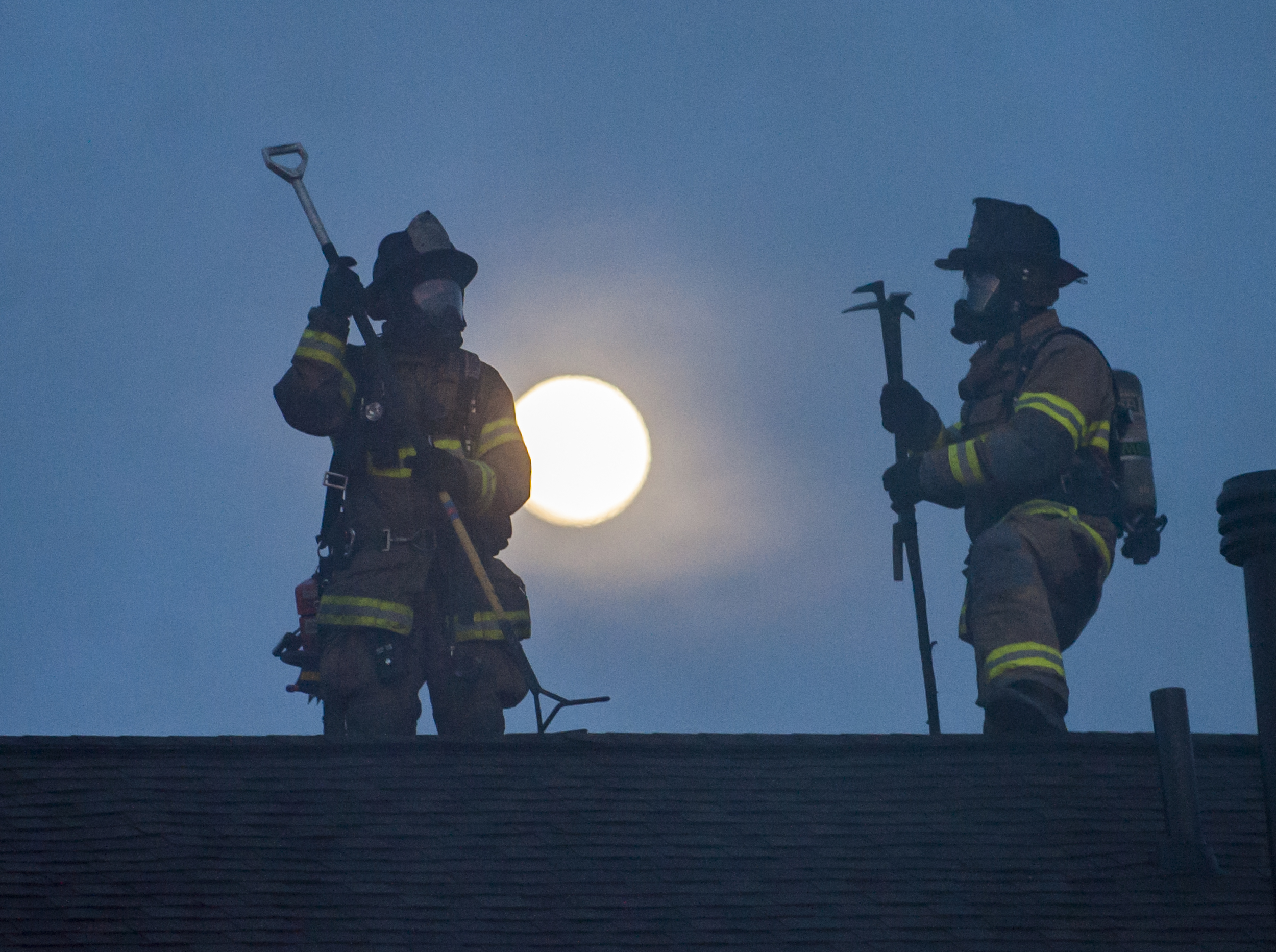 Members of Alpha Fire Co. work on clearing and checking the roof of building 14 of The Park Apartments after the building caught fire on Wednesday, April 20, 2016.