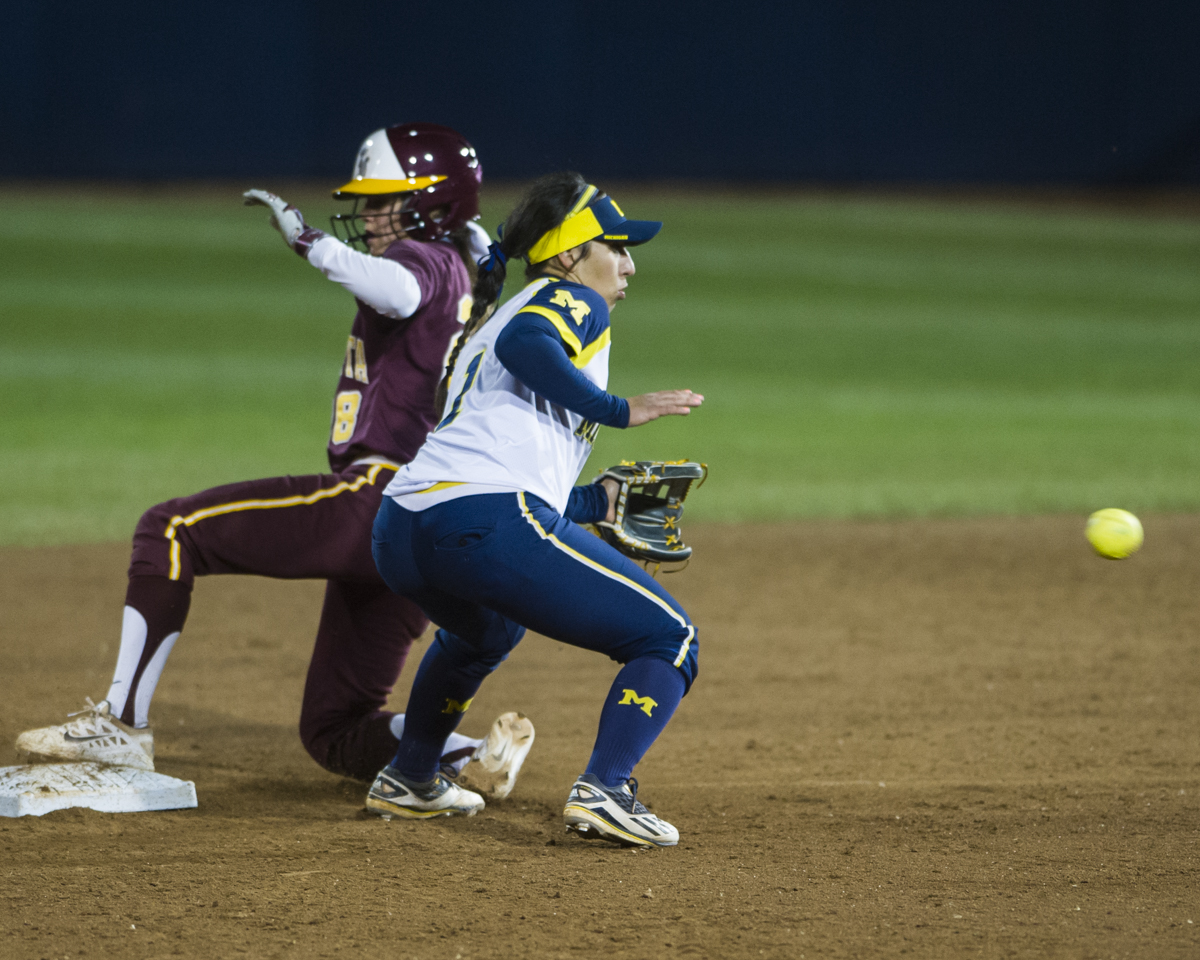 Michigan second baseman Abby Ramirez leans to catch a throw as Minnesota infielder Danielle Parlich slides safely on base during the final game of the Big Ten Tournament at Beard Field on Saturday, May 14, 2016.