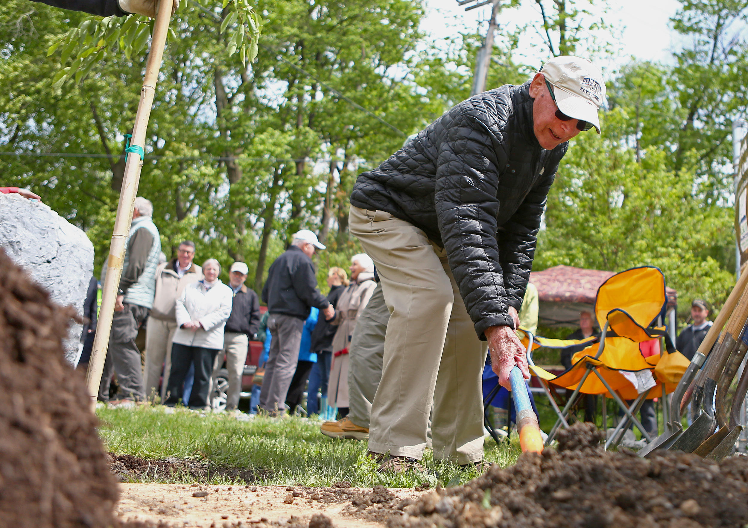 Founder of the Spring Creek chapter of Trout unlimited Joe Humphreys shovels soil onto the tree planted as part of the ceremony recognizing Humphreys and the Trout Unlimited's Thompson Run improvement project at the duck pond located at the intersection of Porter Road and College Avenue on Sunday, May 15, 2016.