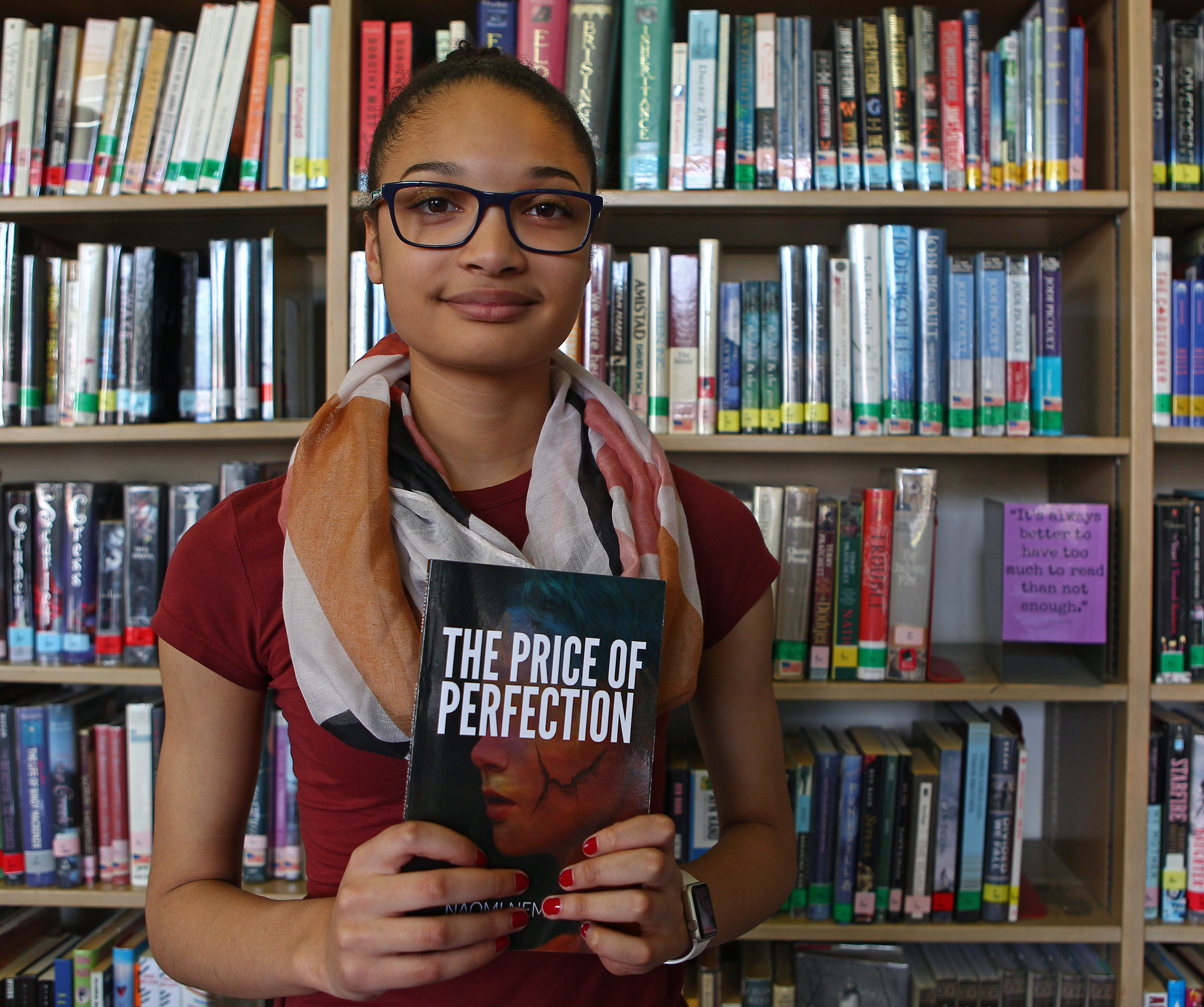 "State College Area High School freshman Naomi Nembhard poses in the school's library with her book ""The Price of Perfection"" on Thursday, May 19, 2016."