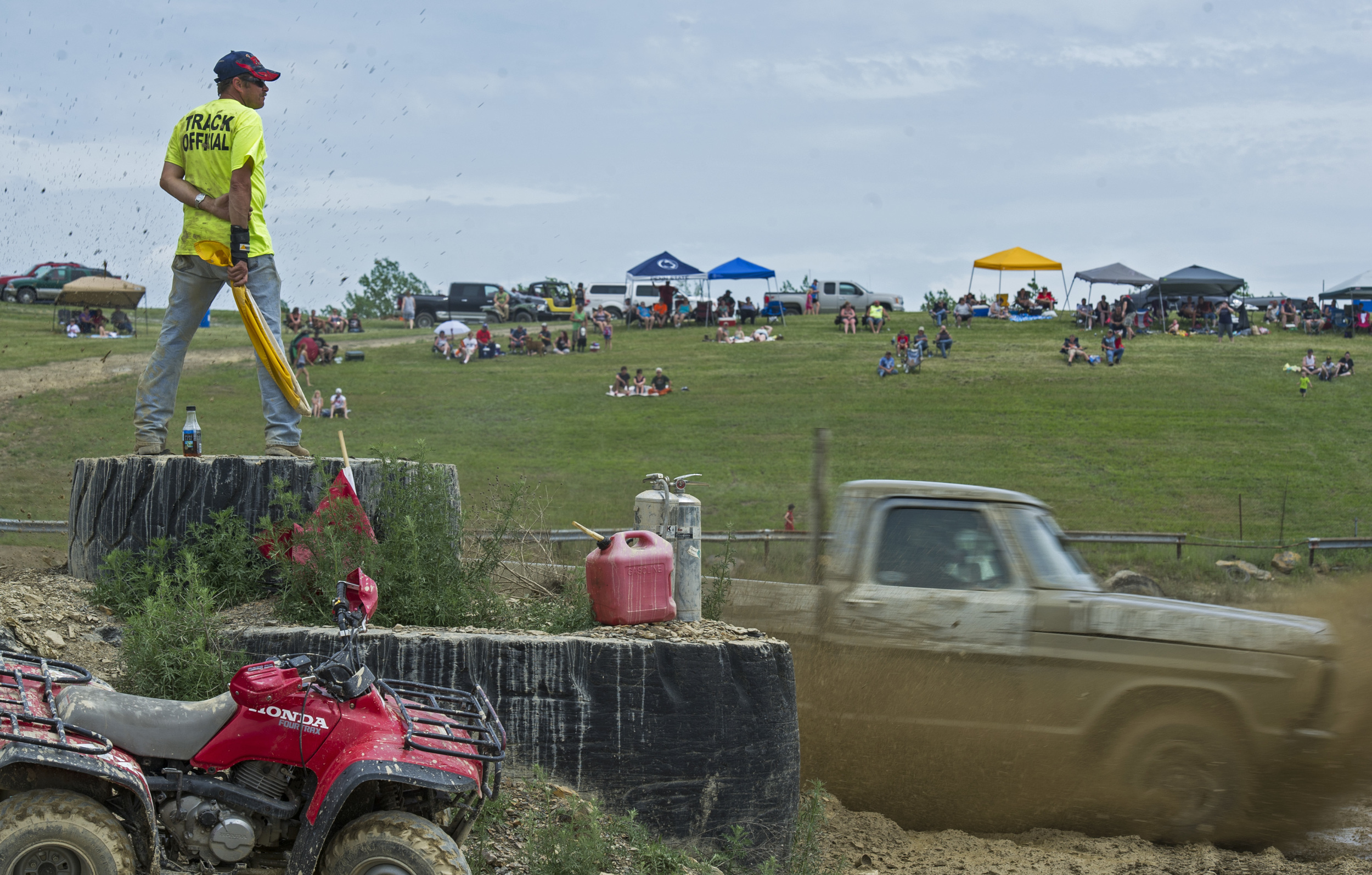 Volunteer track official Patrick Stania watches as Rodney Smith pilots his Ford pickup truck around the Snow Shoe mud track during the Snow Shoe Mud Race on Sunday, May 29, 2016.