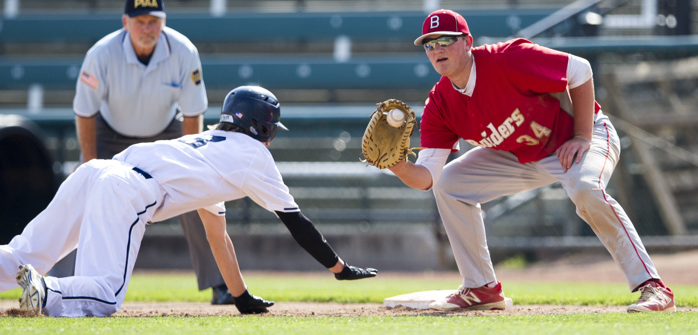 Bellefonte first baseman Logan Mathieu catches a throw from the pitcher after Hollidaysburg left fielder Andrew Moyer slides safely back to base during the PIAA District 6 championship game at Peoples Natural Gas Field on Wednesday, June 1, 2016.