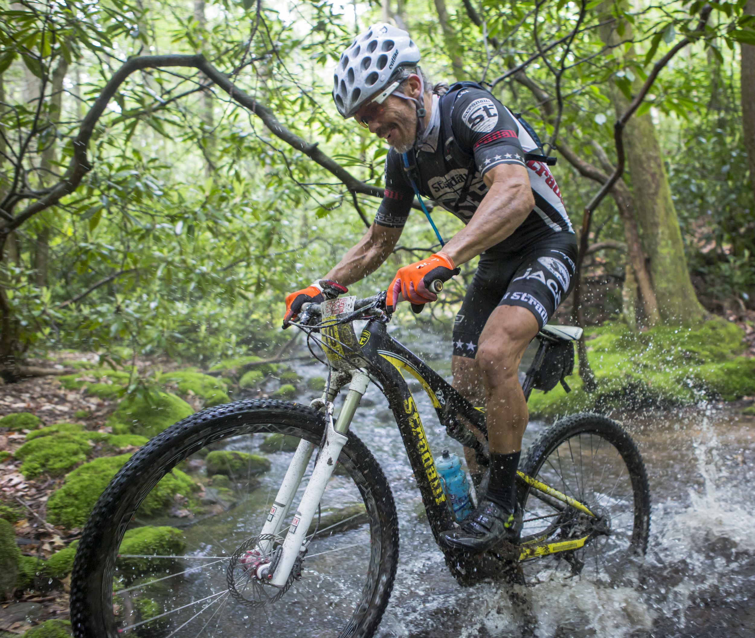 Bob McCarty of the Stradalli team powers through a stream crossing on the Lingle Valley trail during the final stage of the Tran-Sylvania Epic Mountain Bike Ride in Rothrock State Forest on Friday, June 3, 2016.