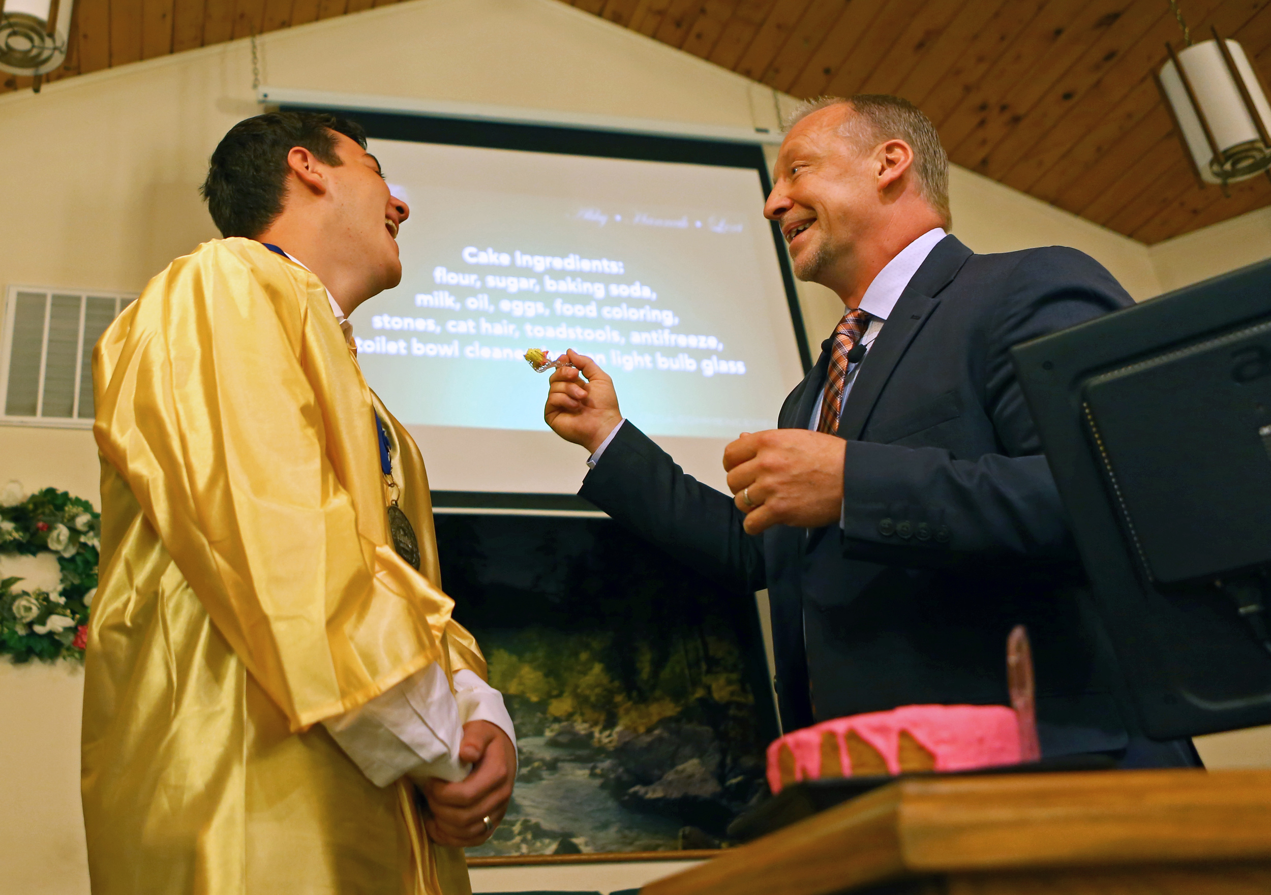 Keynote speaker Kenneth Gore, right, offers a piece of cake to Centre County Christian Academy rising senior Jacob Berzas as part of his address during the commencement ceremony at Calvary Bible Church in Centre Hall on Friday, June 10, 2016.
