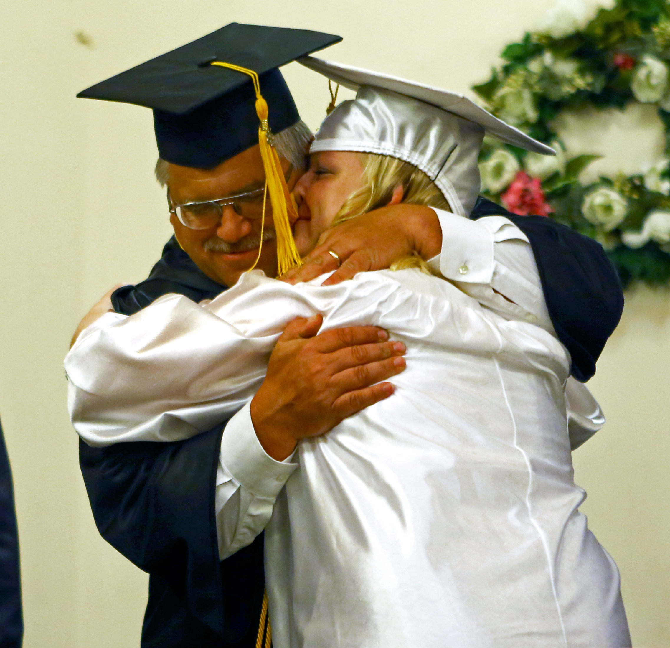 Centre County Christian Academy graduating senior Abby Maholic embraces her father and faculty member Robert Maholic after receiving her diploma during the commencement ceremony at Calvary Bible Church in Centre Hall on Friday, June 10, 2016.