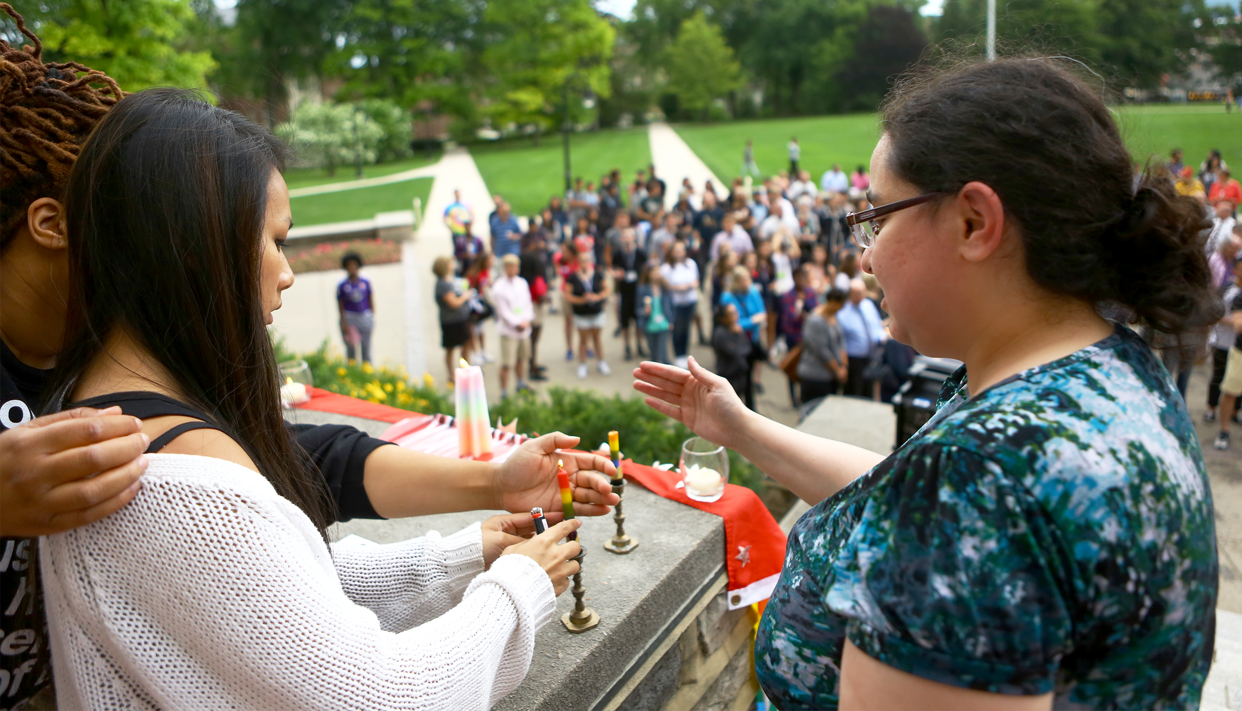Lianne Luu, left, and Lia Talmas light candles on the steps of Old Main to start the candle light vigil honoring the victims of the Orlando, Florida shooting victims on Monday, June 13, 2016.