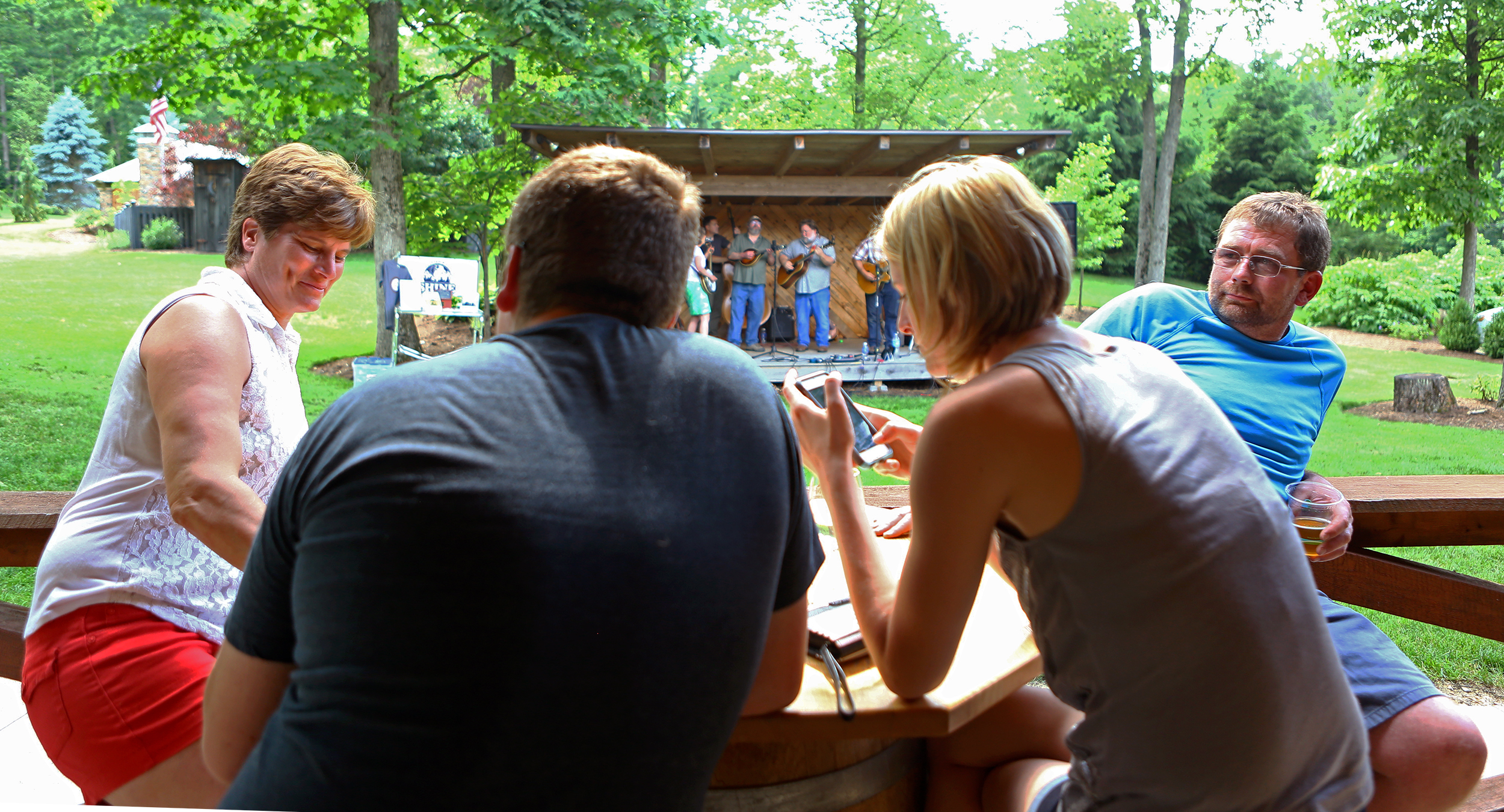 Matt Carney (far right) sits with his family as the Tussey Mountain Moonshiners perform during the Father's Day barbecue at Seven Mountains Wine Cellars on Sunday, June 19, 2016.