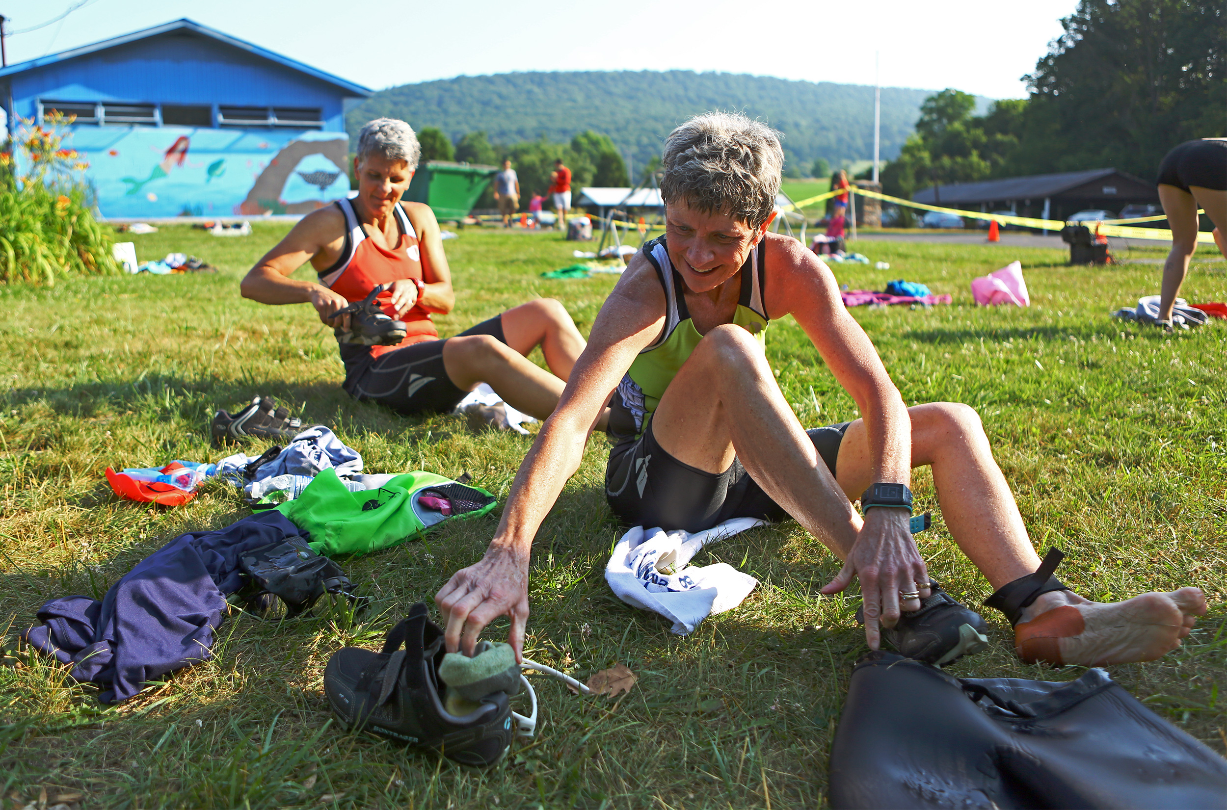 Phillis Sieber,right, and Tammi Christini, left, change into their cycling shoes and equipment during the Millheim Pool Sprint Triathlon outside of the Millheim Pool on Saturday, June 25, 2016.