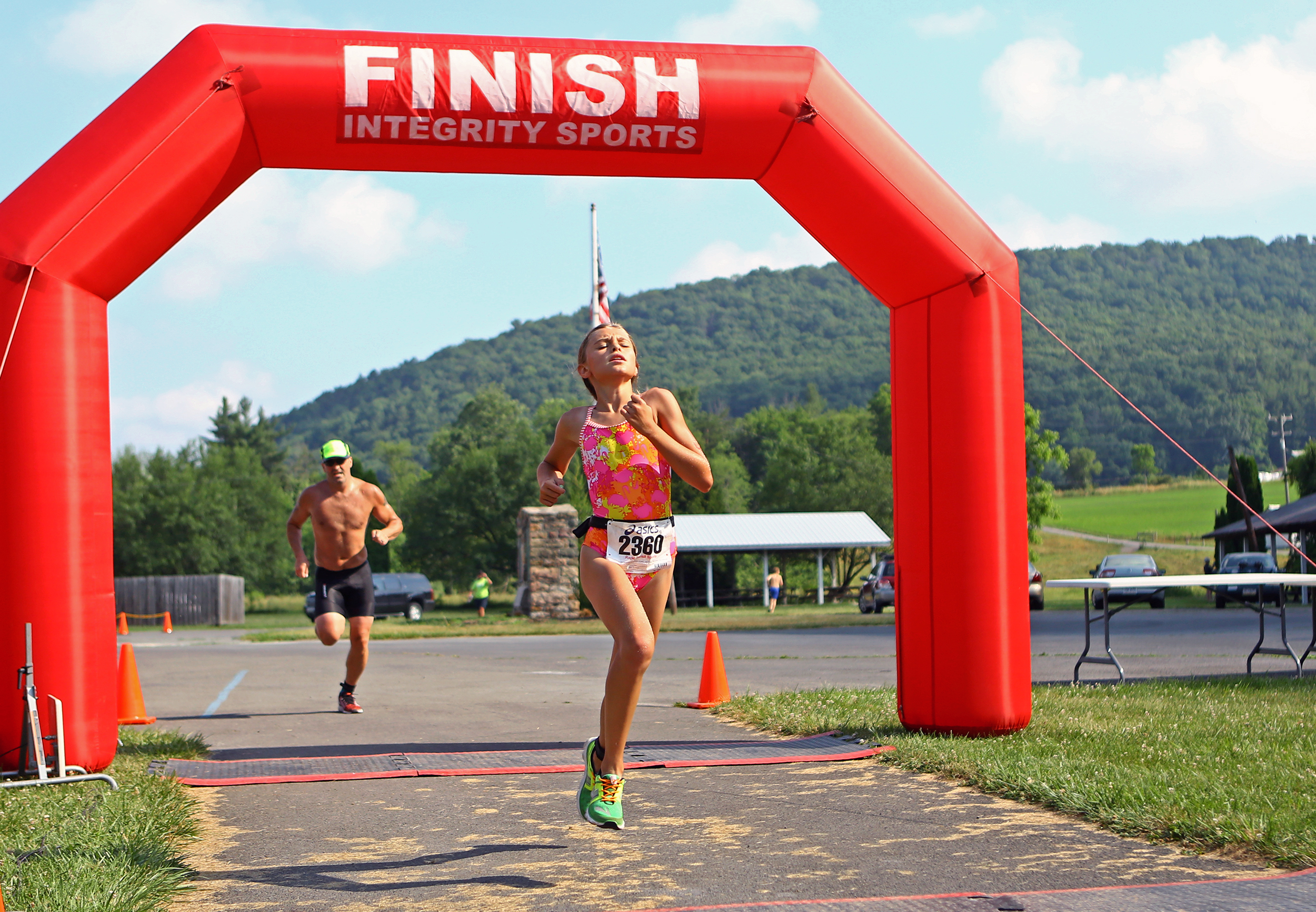 Marlee Kwasnica of State College crosses the finish line at Millheim Pool to complete the Millheim Pool Sprint Mini Triathlon with a time of 48:21 on Saturday, June 25, 2016.