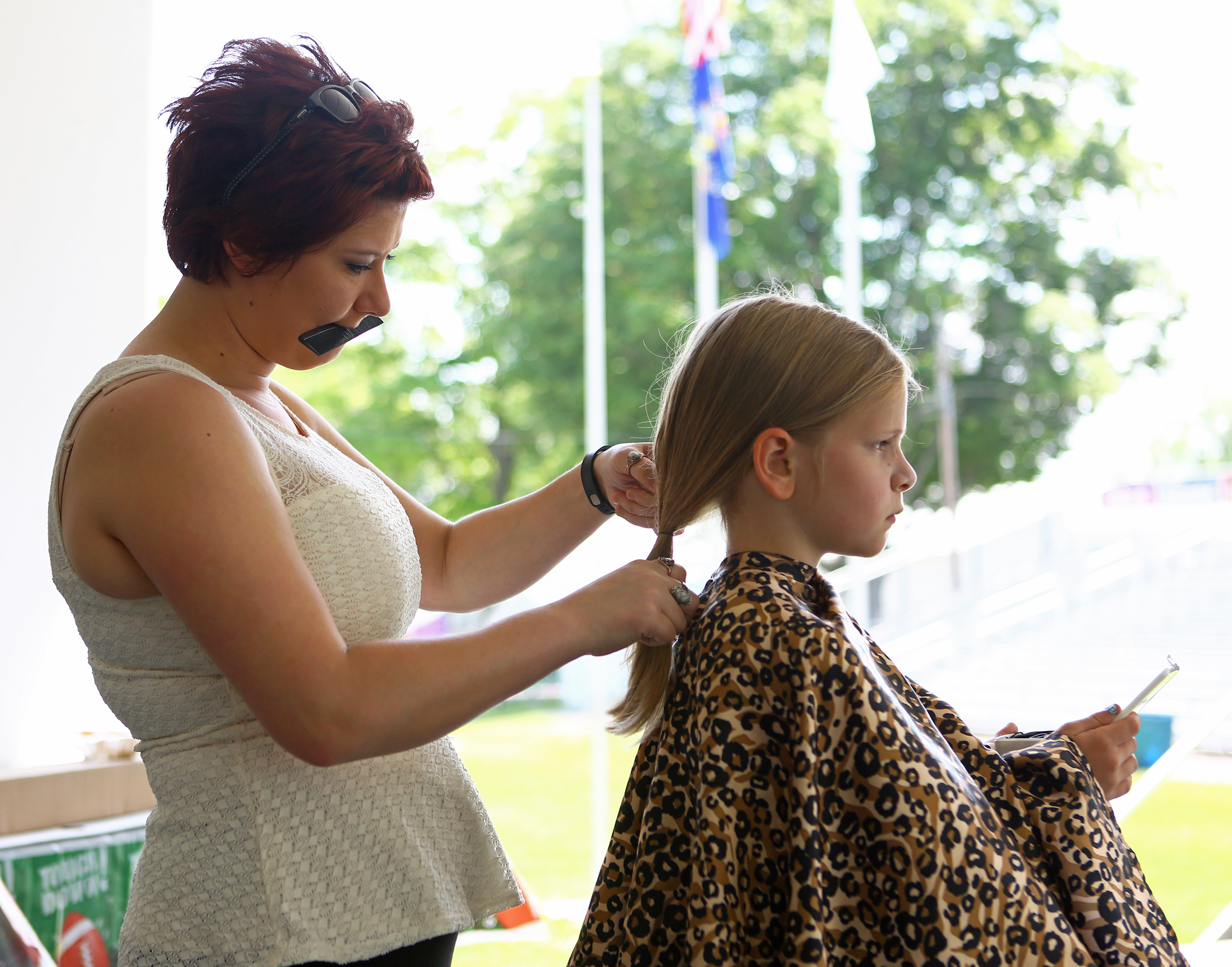 Desiree Stitzer of Holiday Hair salon prepared a ten inch section of Ann Weikert's hair to be donated to Pantene hair donations on the grand stand of the Grange Fair Grounds during the Happy Valley Relay for Life on Saturday, June 25, 2016.