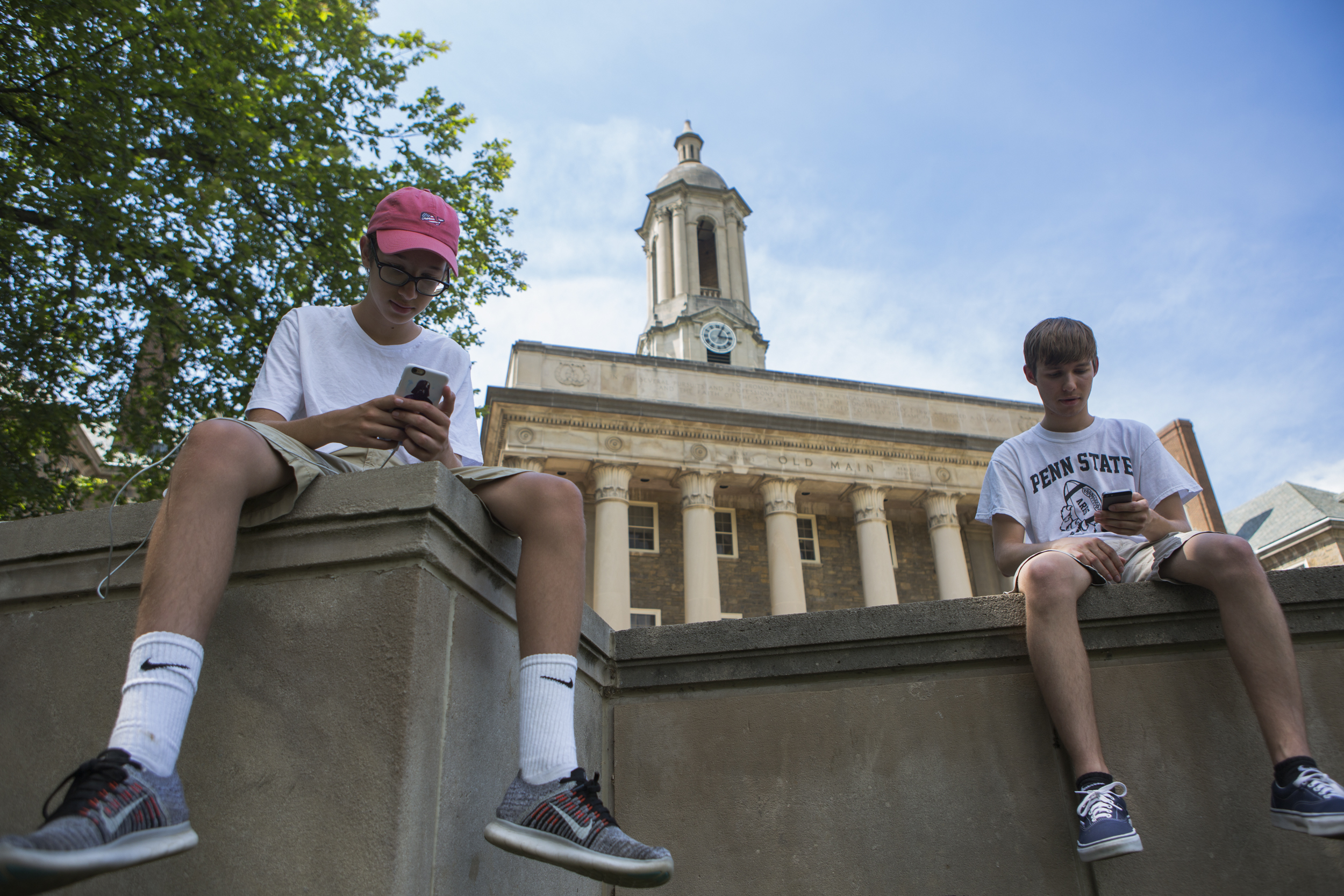 State College local brothers Sam Woytowich, left, and Zach Woytowich play Pokémon Go on the steps of Old Main on Monday, July 18, 2016.