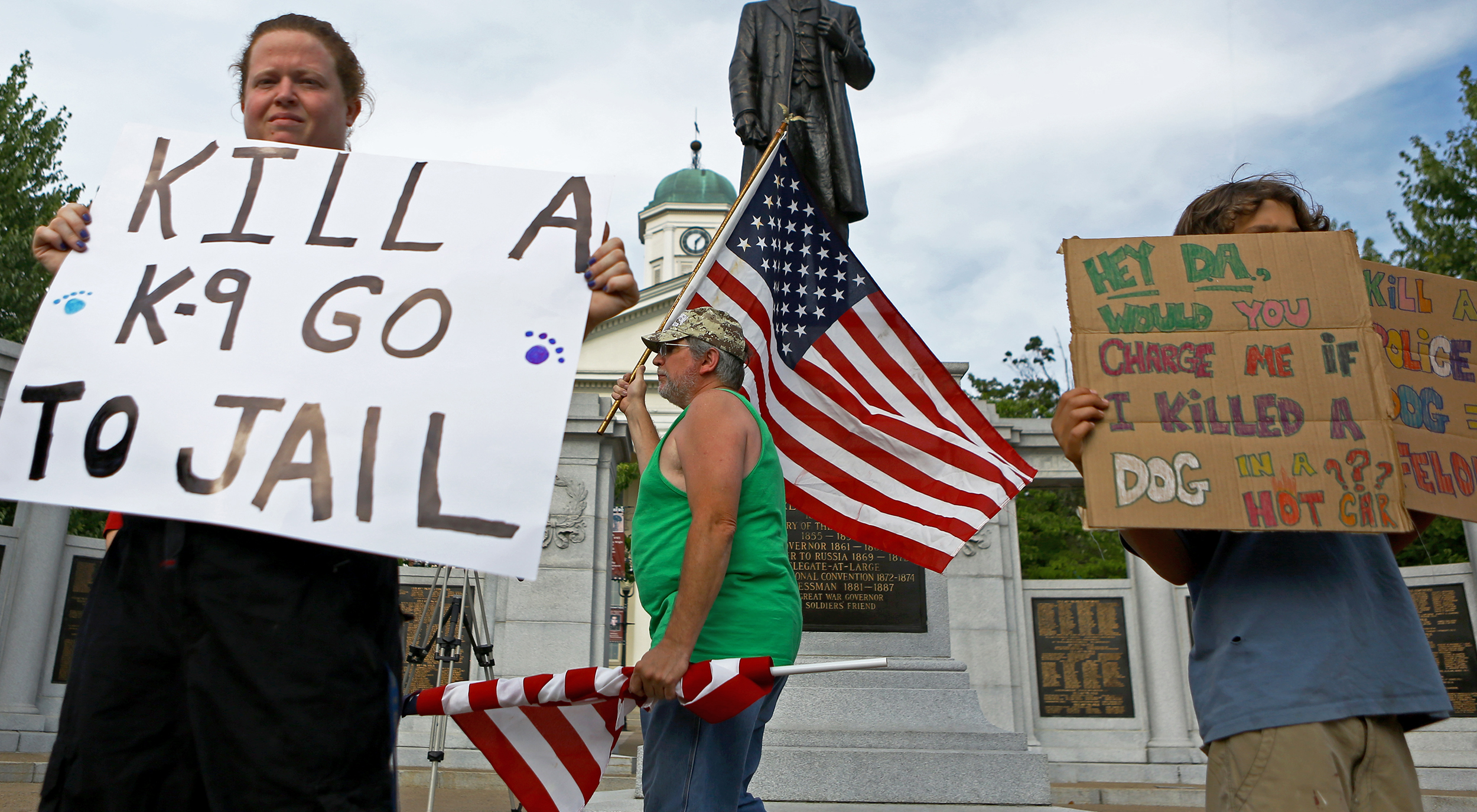 Tim Wian, center, of Phillipsburg flies the American flag as other Centre County residents hold signs on Allegheny Street in Bellefonte on Monday, July 18, 2016 calling for justice for Totti, a Department of Corrections drug detection dog that died after being locked in a hot car for over two hours.