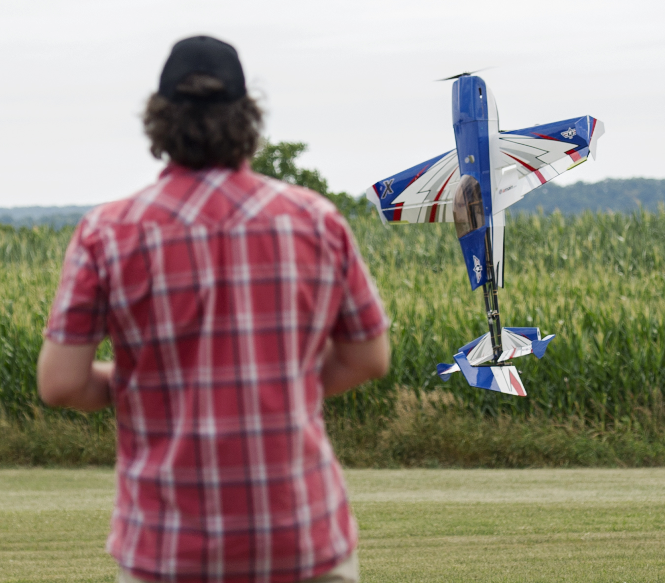 "Arron Bates of West Decantur holds his custom build radio control plane, called ""The Honey Badger"" at a hover over the Centre Airpark's runway during the State College Radio Control Club Air Show on Sunday, July 24, 2016."