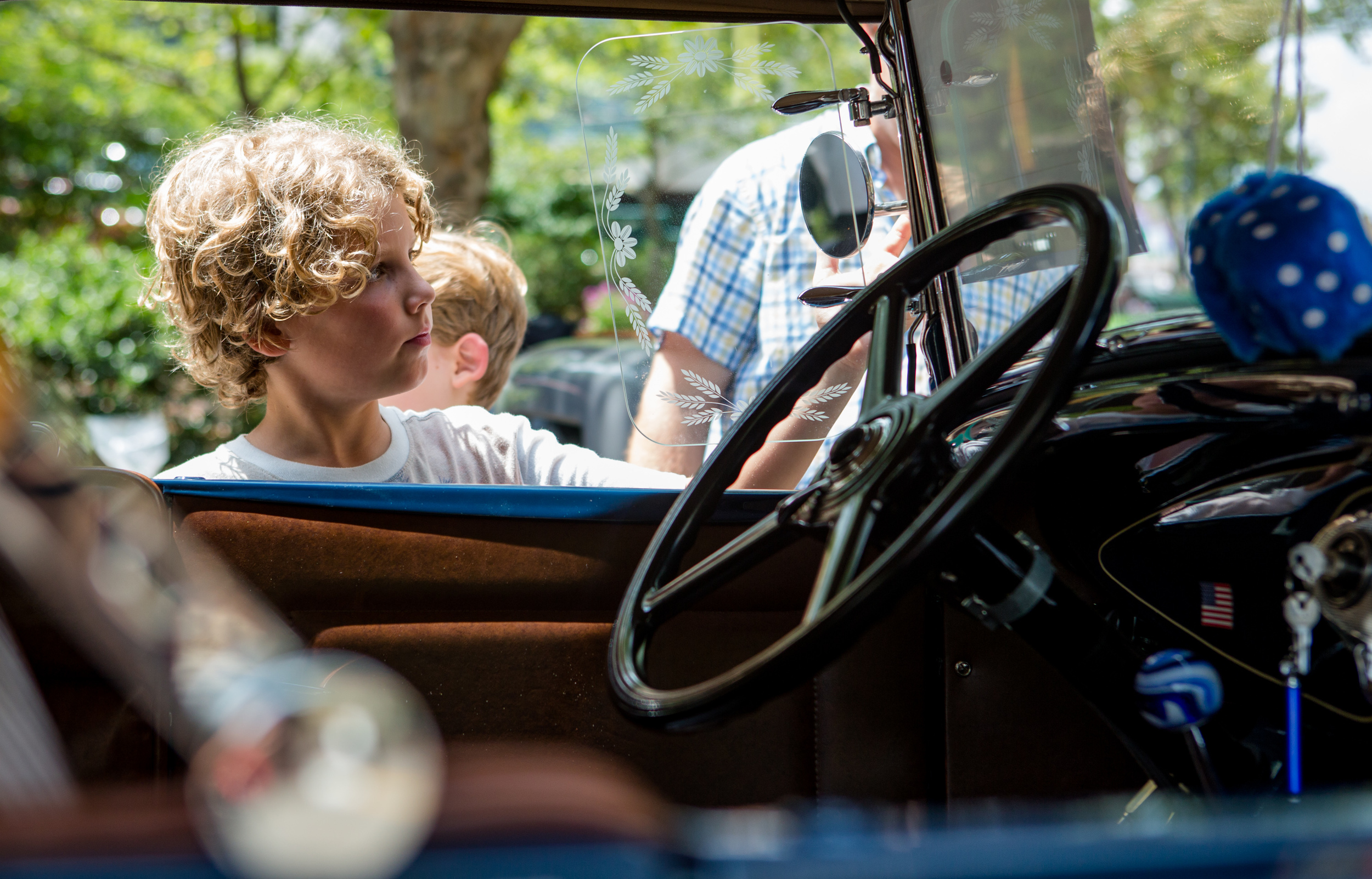 Ben Garthwaite of State College examines the side mirrors on a restored 1930 Ford Deluxe Roadster during the Last Cruise Car Show on Allen Street on Sunday, July 31, 2016