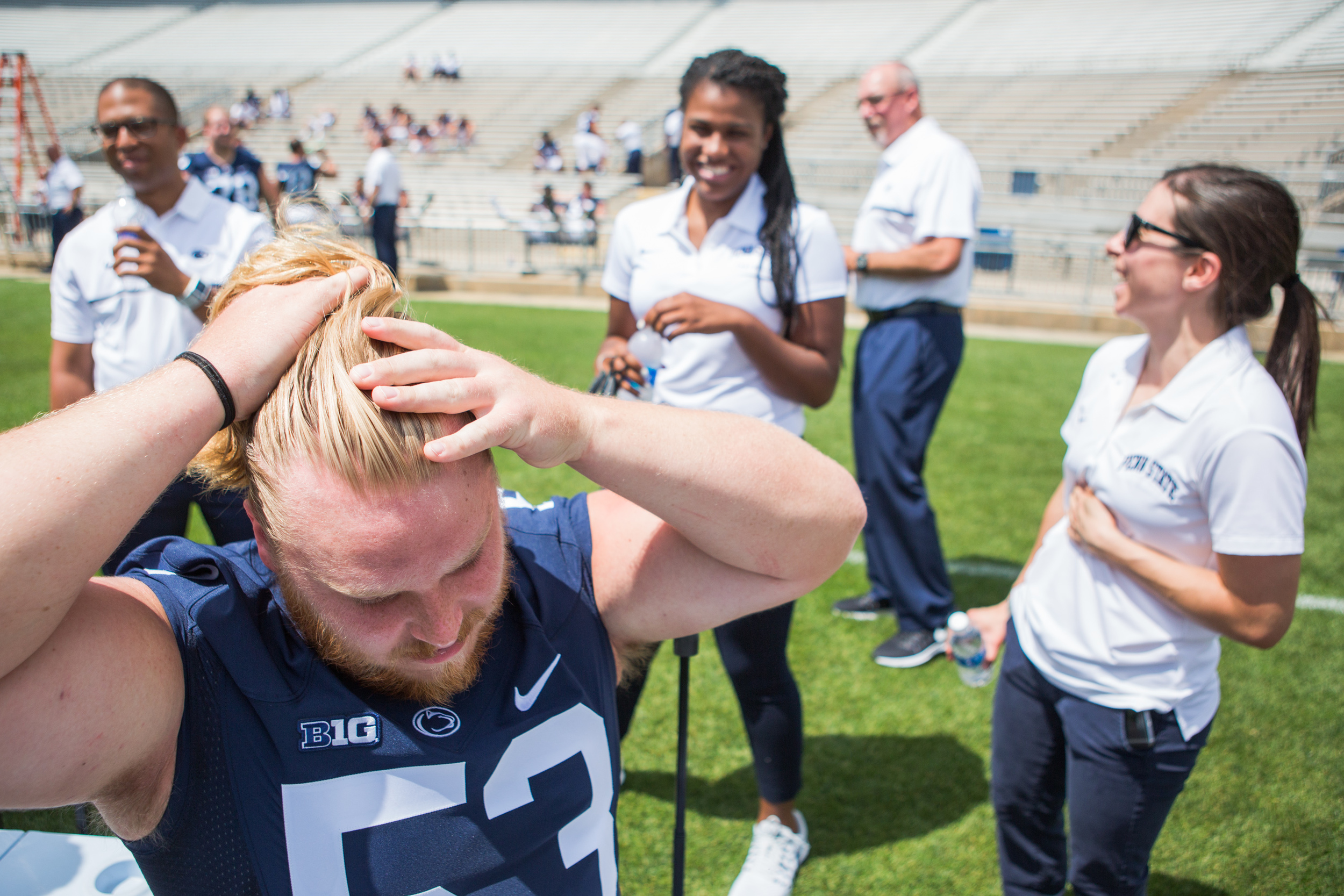 Graduate student Derek Dowrey shows assistant learning specialist Chelsea Holmes, center, and assistant athletic trainer Madeleine Scaramuzzo, right, how he ties his hair into a bun during the football team's photo day on the field of Beaver Stadium on Sunday, Aug. 7, 2016.