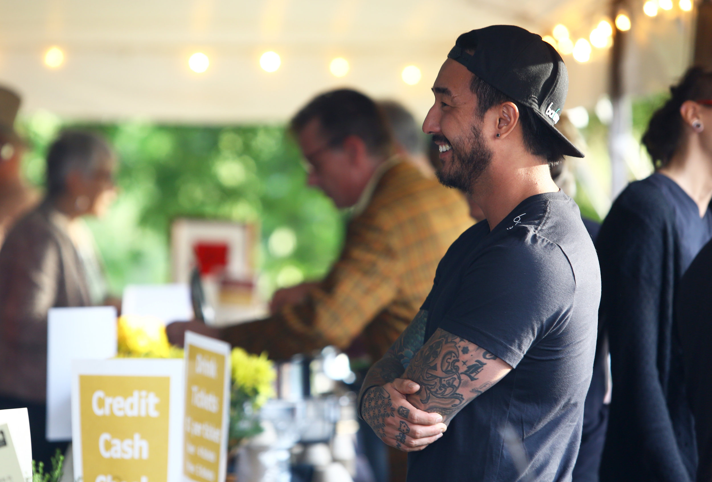 CJ Jang of Balance Grill smiles as he jokes with coworkers during the Toledo Grows Harvest Market Dinner held at the Toledo Botanical Gardens on Thursday, Sept. 15, 2016.