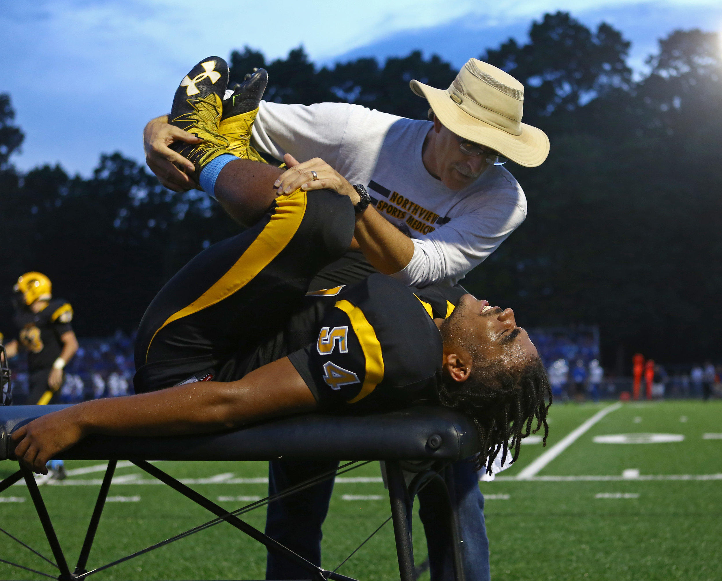 Northview High School athletic trainer Jon Engel helps sophomore defensive end Jayden Bolden stretch after a minor upper leg injury during the game against Anthony Wayne High School at Northview High School in Sylvania on Friday, Sept. 16, 2016. Anthony Wayne High School won the game 35-14.