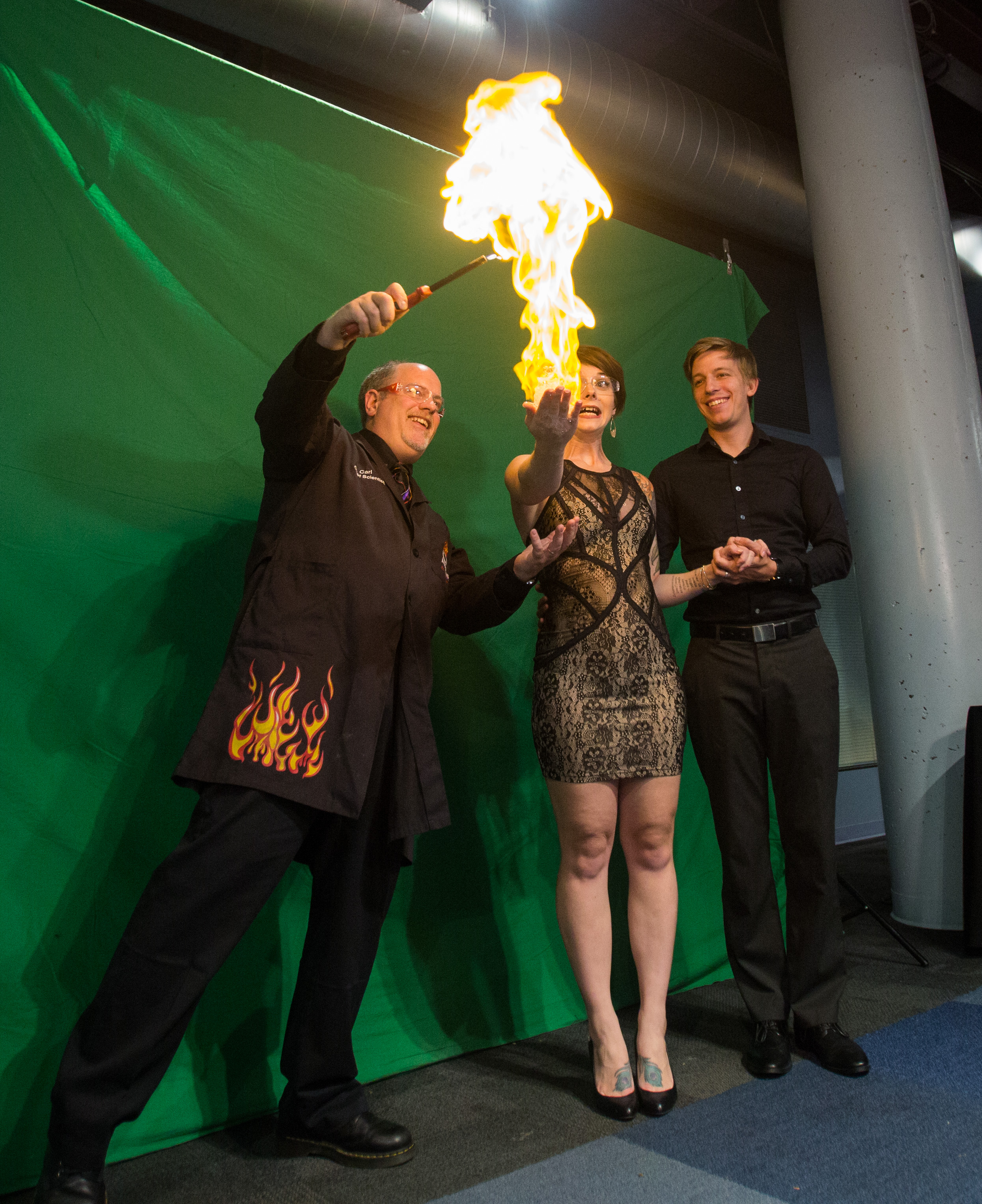 Imagination Station chief scientist Carl Nelson lights the methane filled bubbles in Bri Gibson's hand to take a photo with Ben Gibson during the Bash 7 fundraiser at Imagination Station in downtown Toledo on Saturday, Sept. 17, 2016.